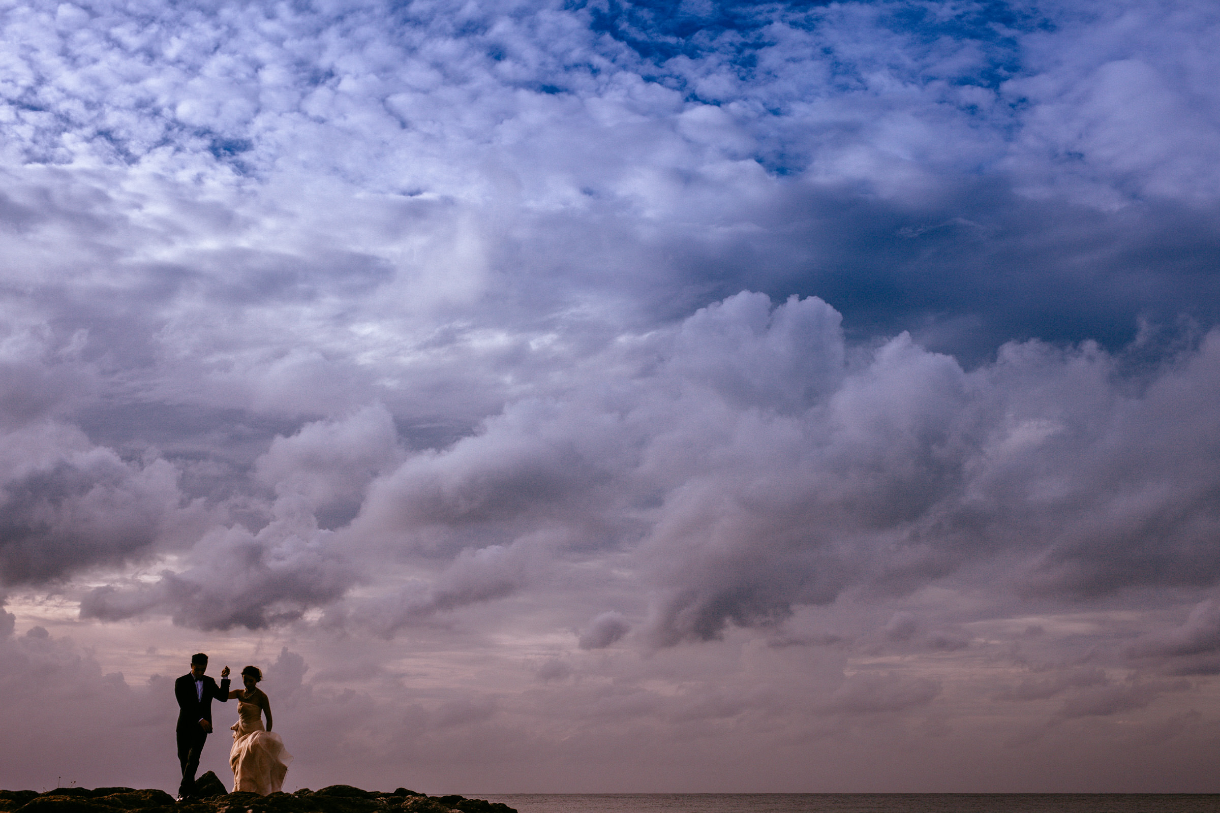 Couple against epic cloudscape - Photo by Wainwright Weddings