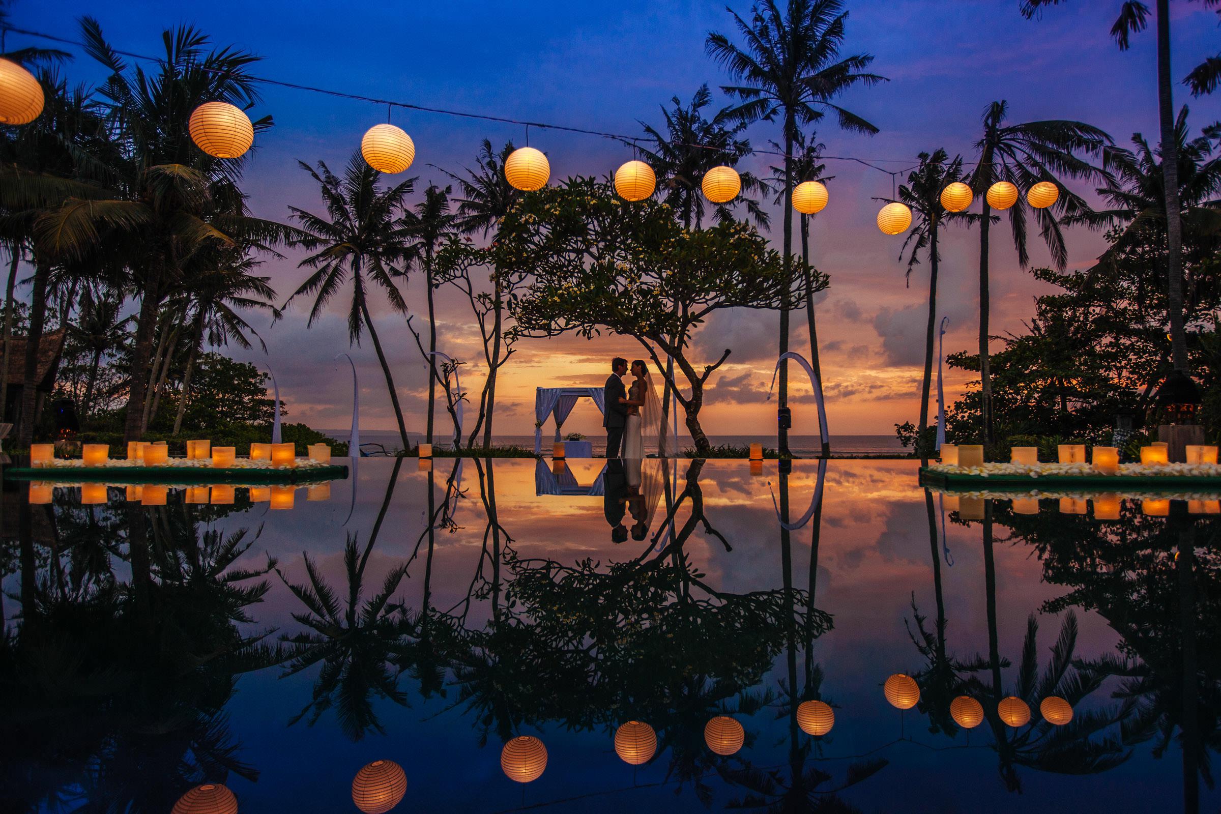 Couple against lanterns at sunset - Photo by Wainwright Weddings