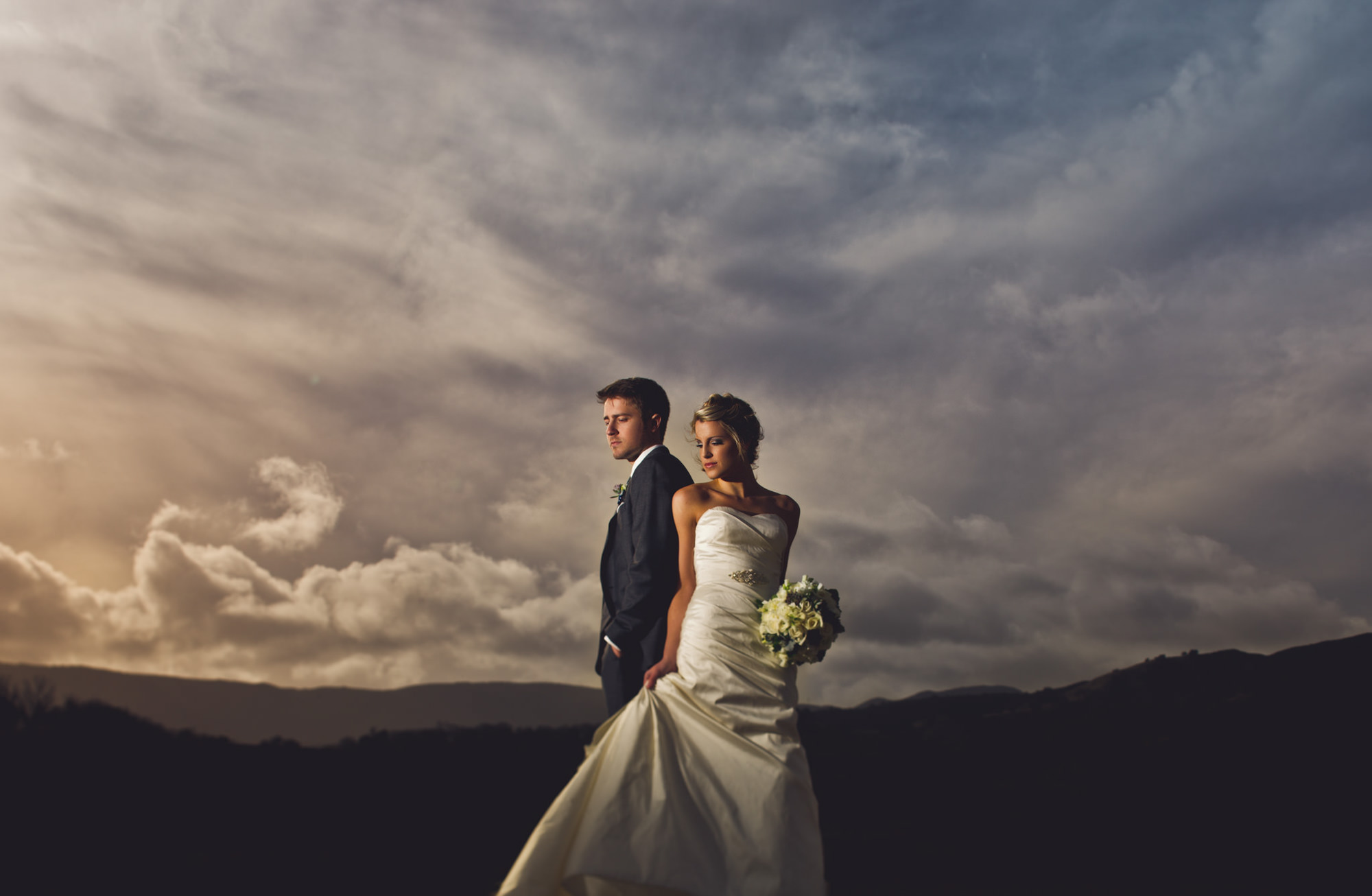 Portrait of bride and groom against dusk sky, by Jeff Newsom