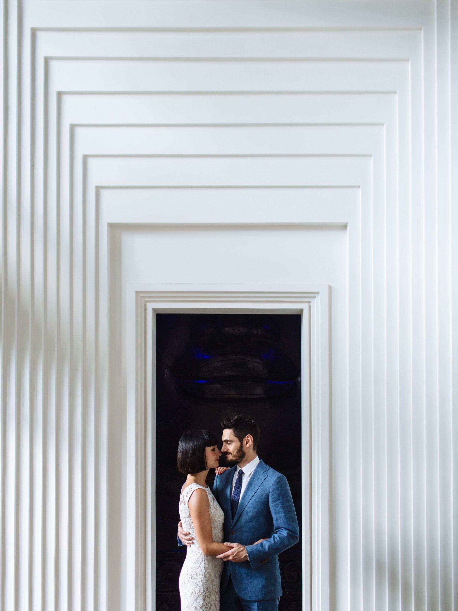 Couple in elaborate modern doorway - Photo by Wainwright Weddings