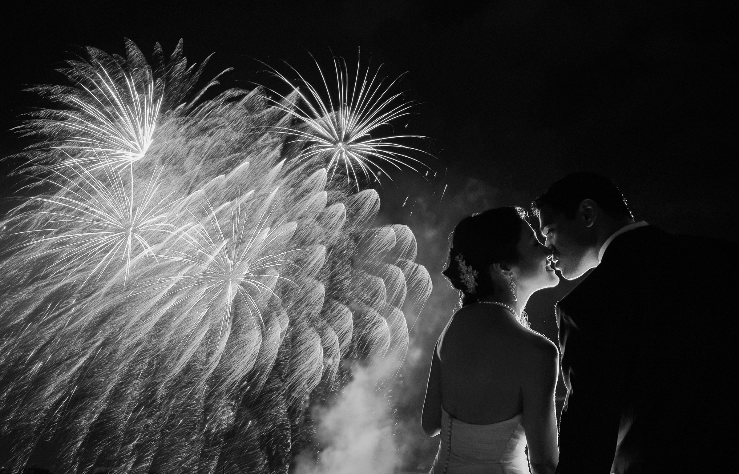 Couple kiss while fireworks display - photo by 37 Frames