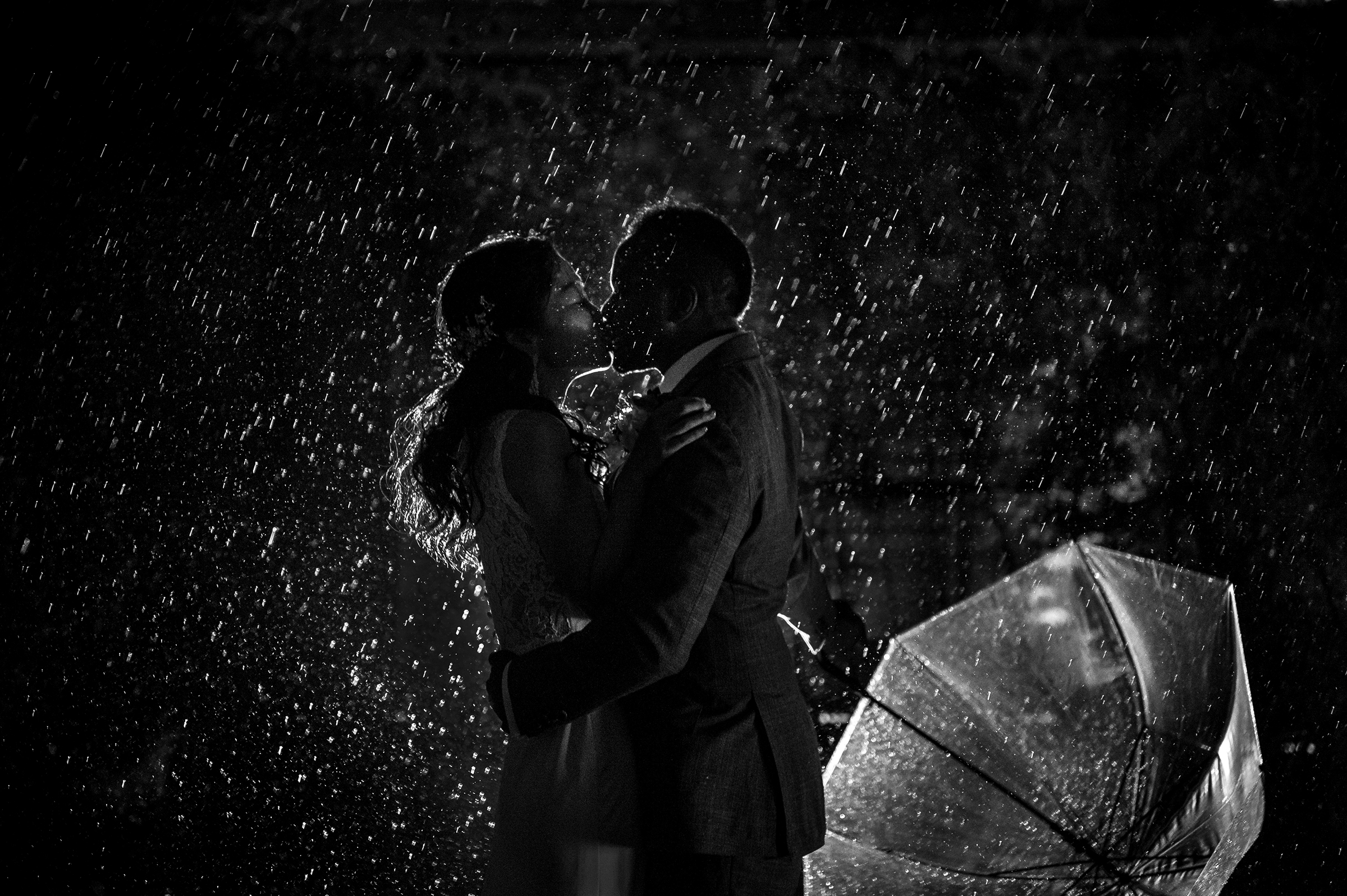 Couple kissing in the rain with umbrella nearby - photo by 37 Frames