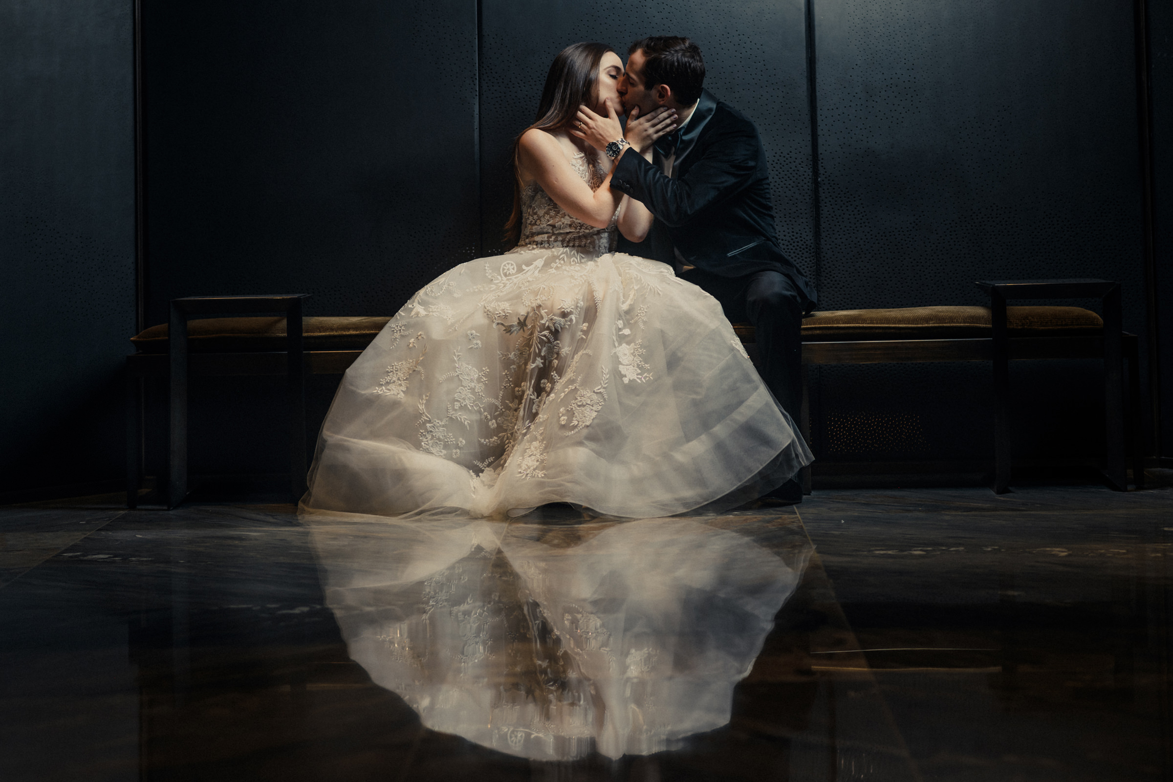 Couple kissing with bride's dress reflected in floor - Photo by El Marco Rojo