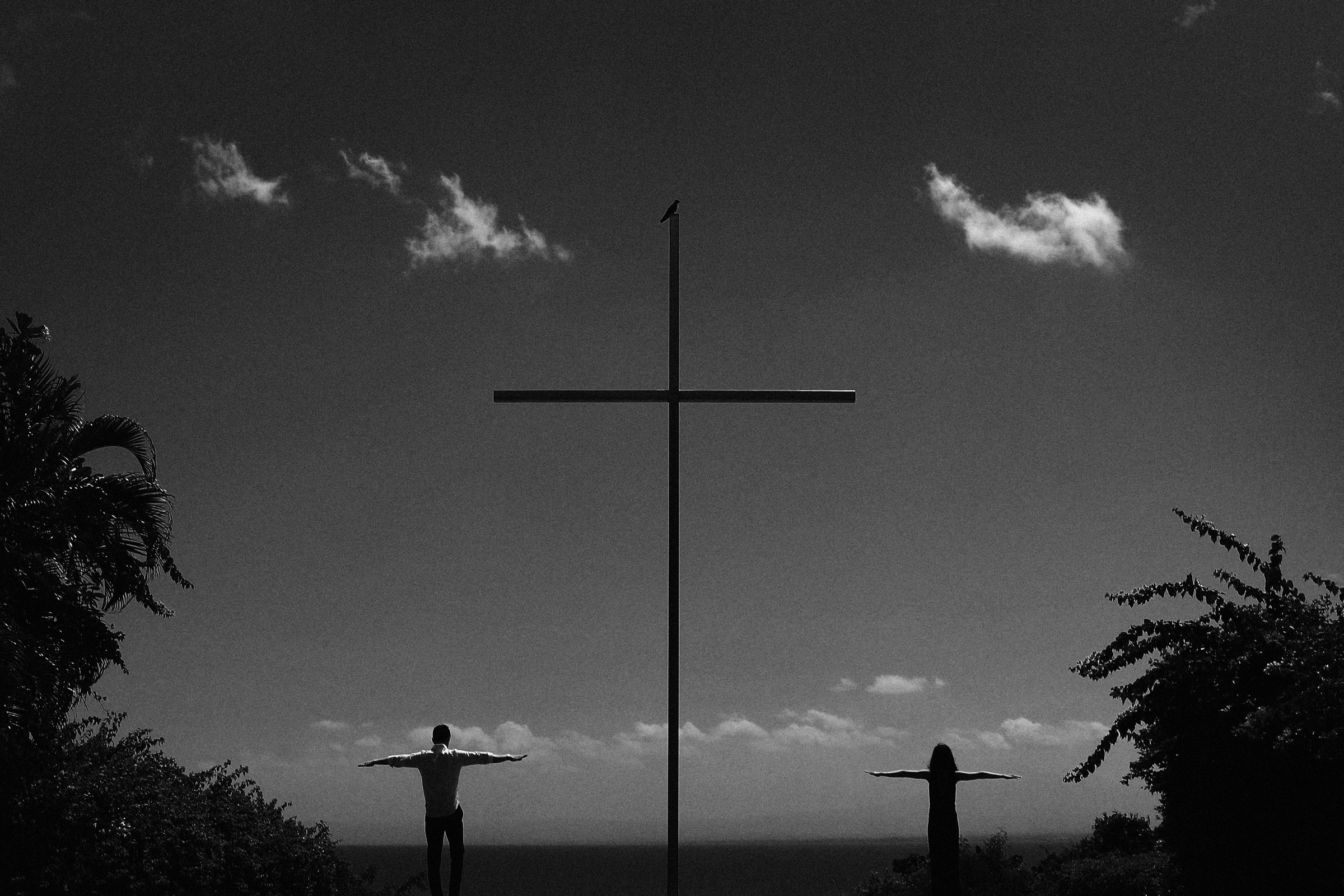Moody portrait of bride and groom engagement portrait next to cross, by Franck Boutonnet