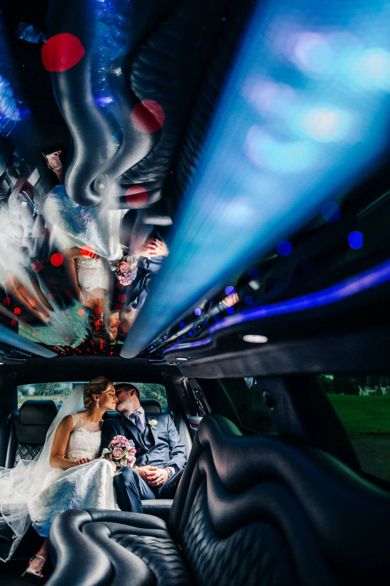 Reflection of bride and groom in limousine ceiling - photo by Ken Pak