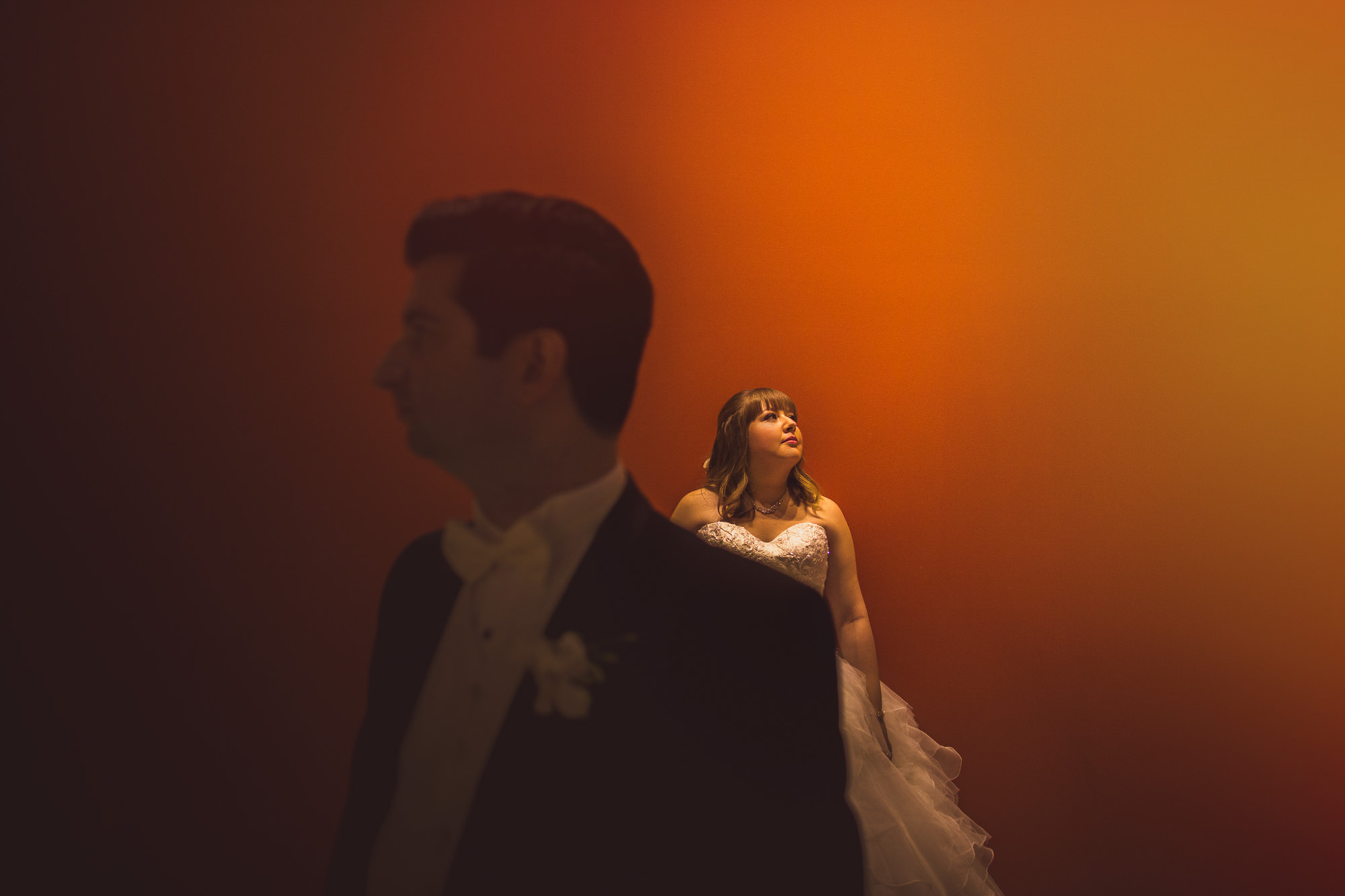 Creative portrait of bride in background with groom in foreground, by Jeff Newsom