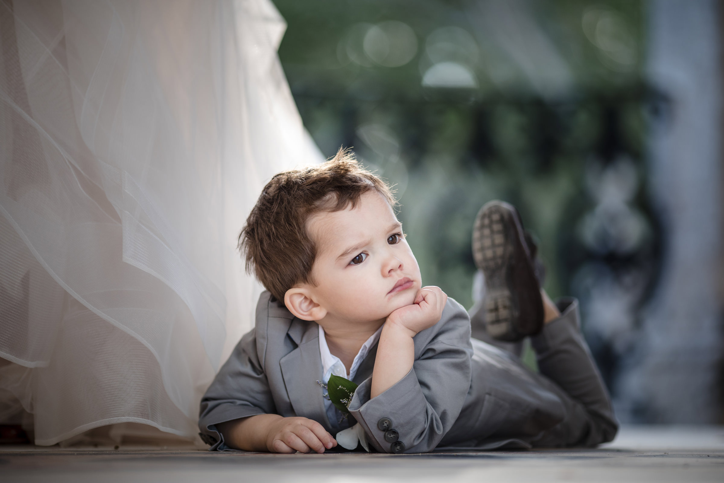 Cute ringbearer on tummy next to bride - Photo by Susan Stripling Photography