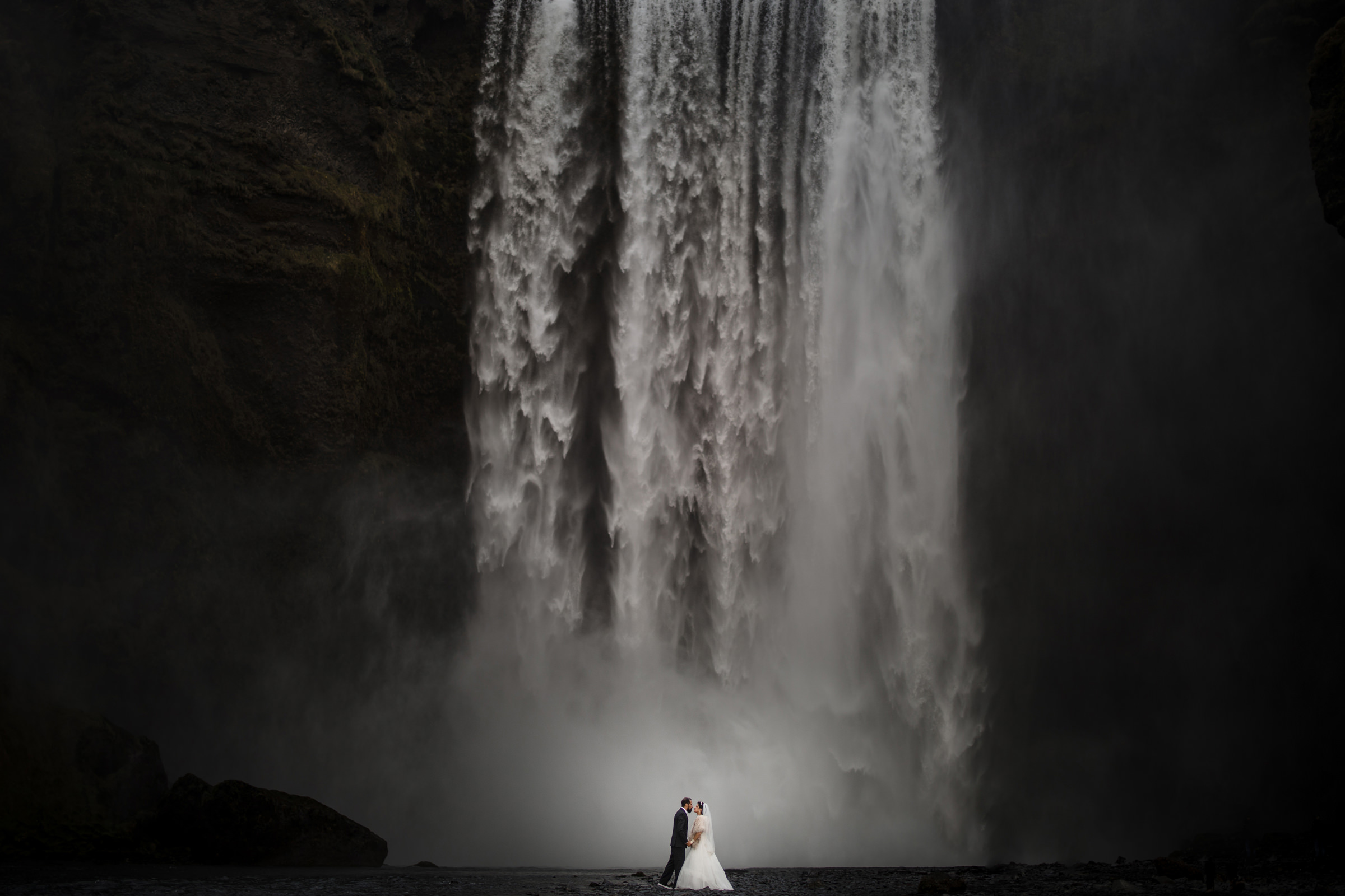 Bride and groom in front of dramatic waterfall - Photo by Susan Stripling Photography