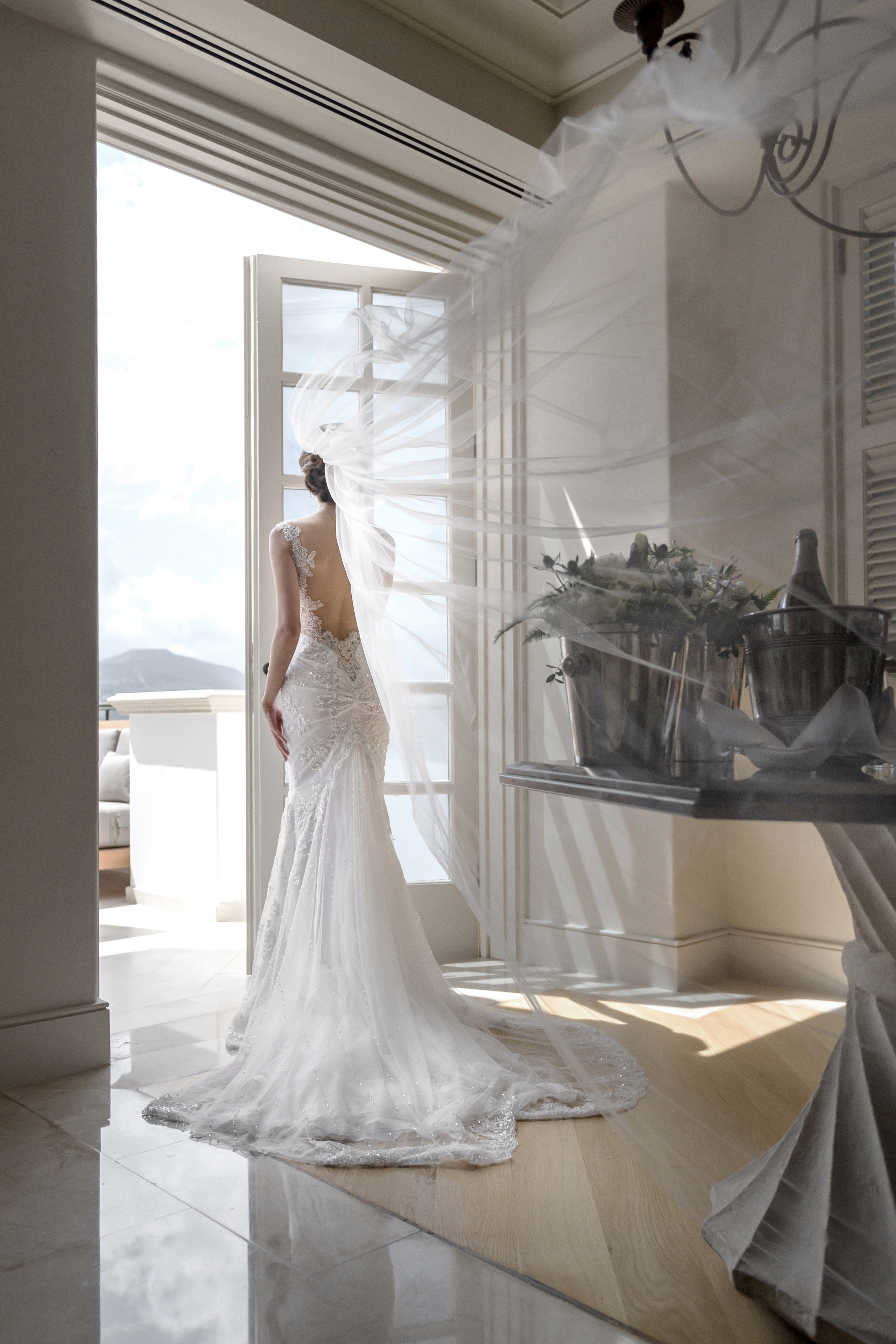 Elegant bride at balcony doors - photo by 37 Frames