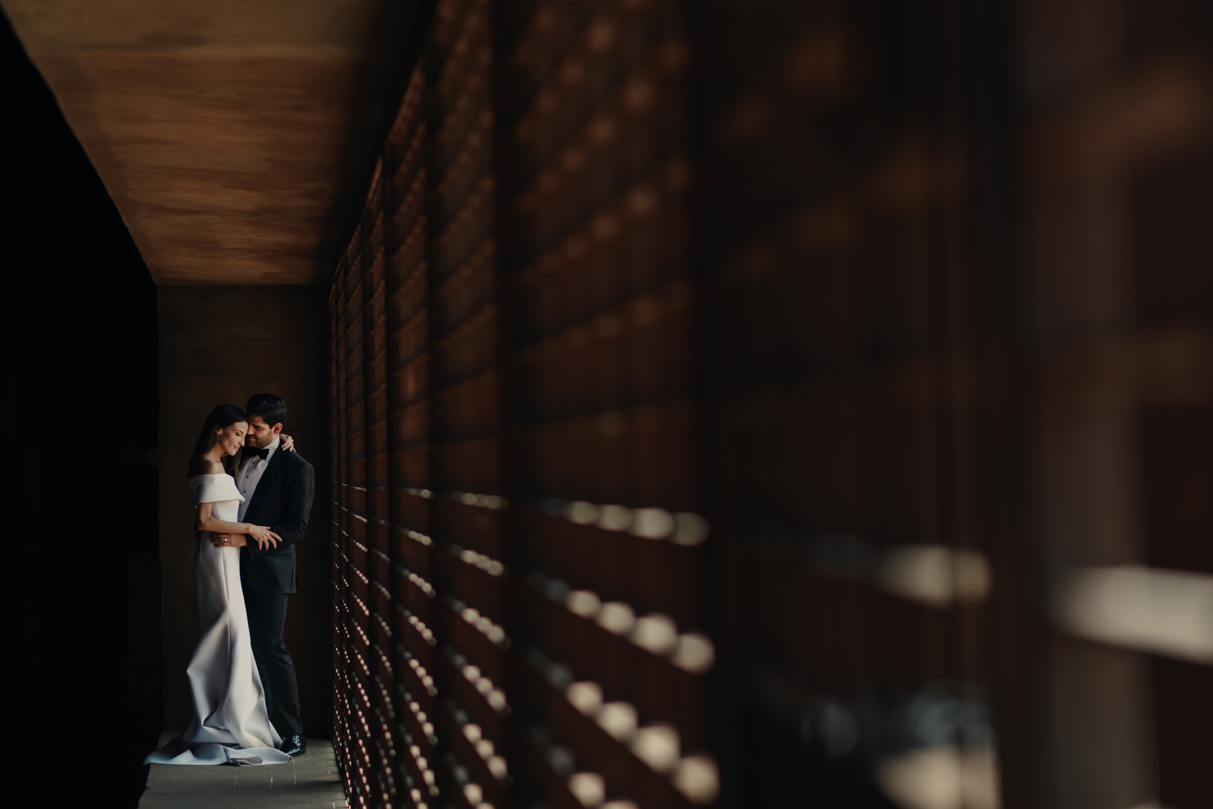 Bride and groom in hallway with slatted wall, by Victor Marti, El Marco Rojo