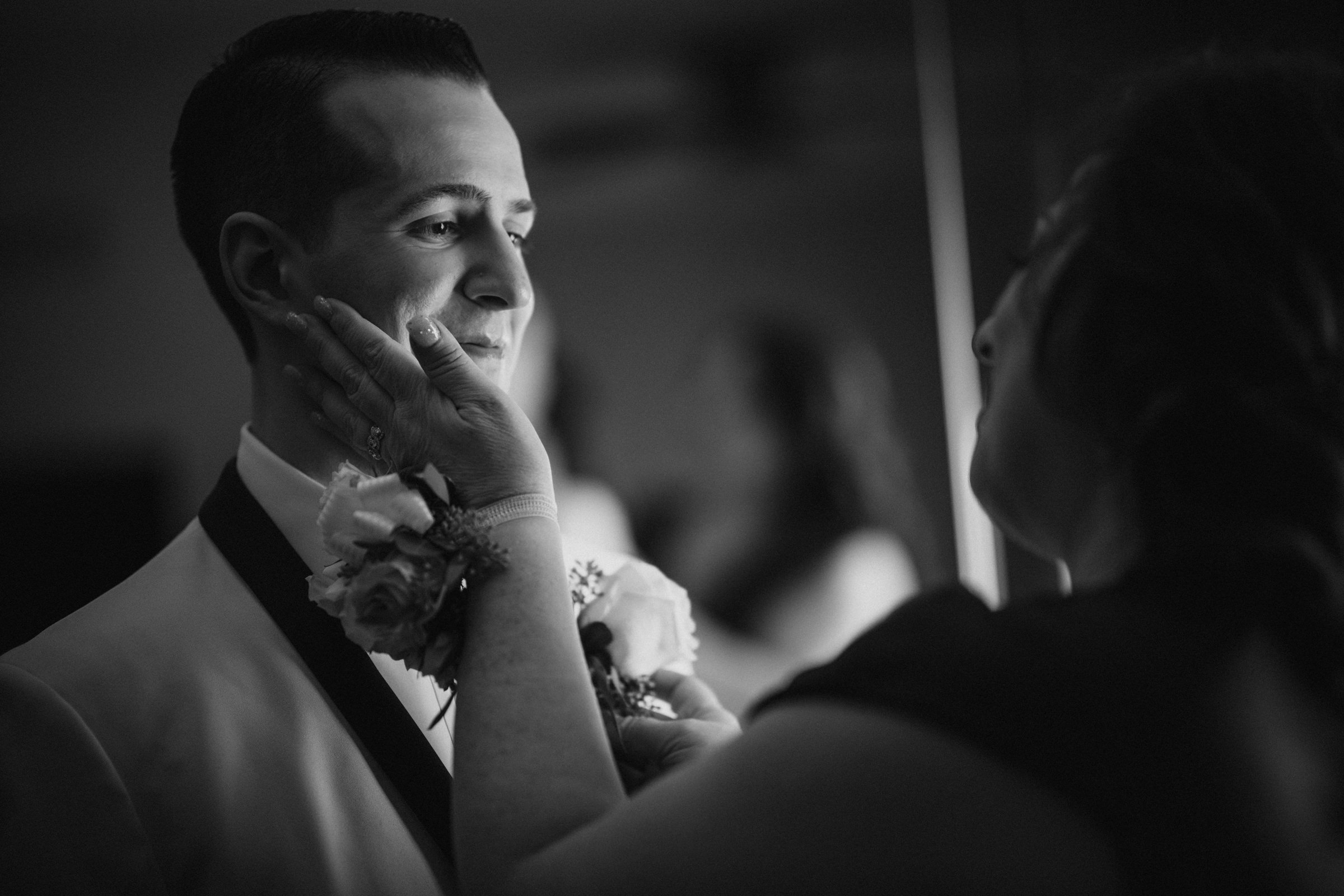 Mother of groom tenderly touches grooms face - Photo by Susan Stripling Photography