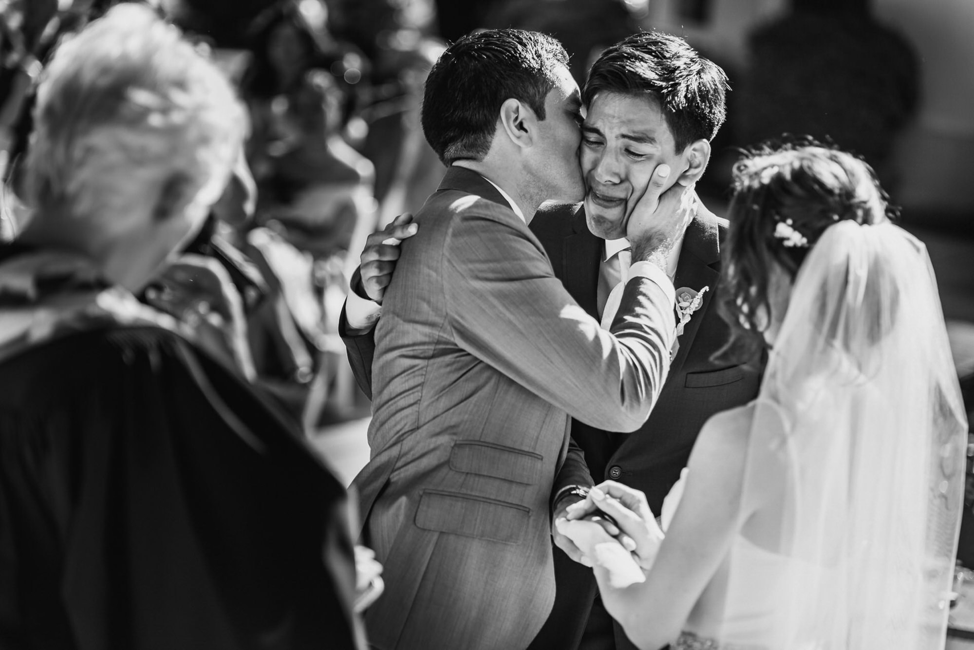 Emotional portrait of dad kissing groom - photo by Ken Pak
