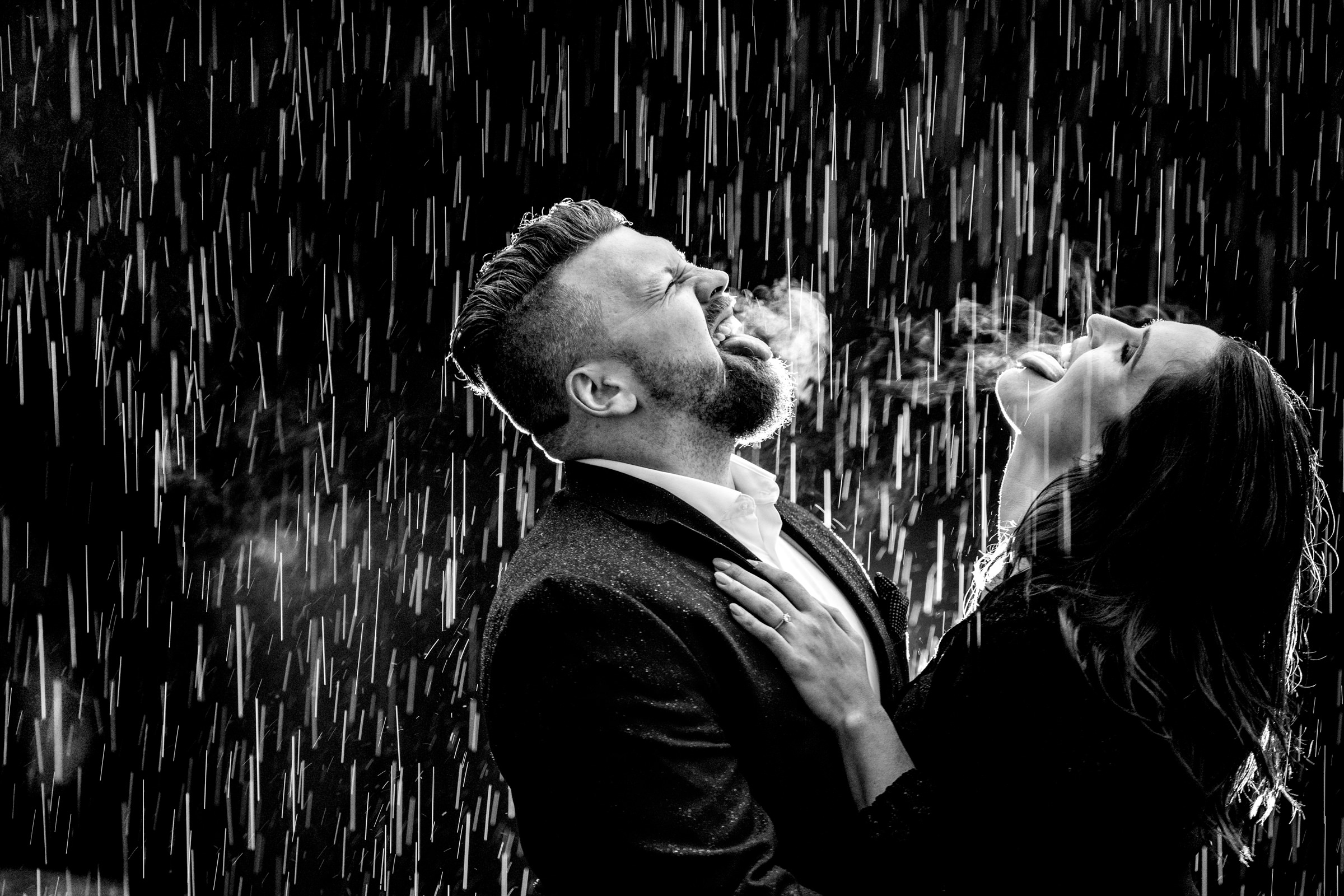 Engagement photo of couple sticking their tounges out in the rain by Bee Two Sweet