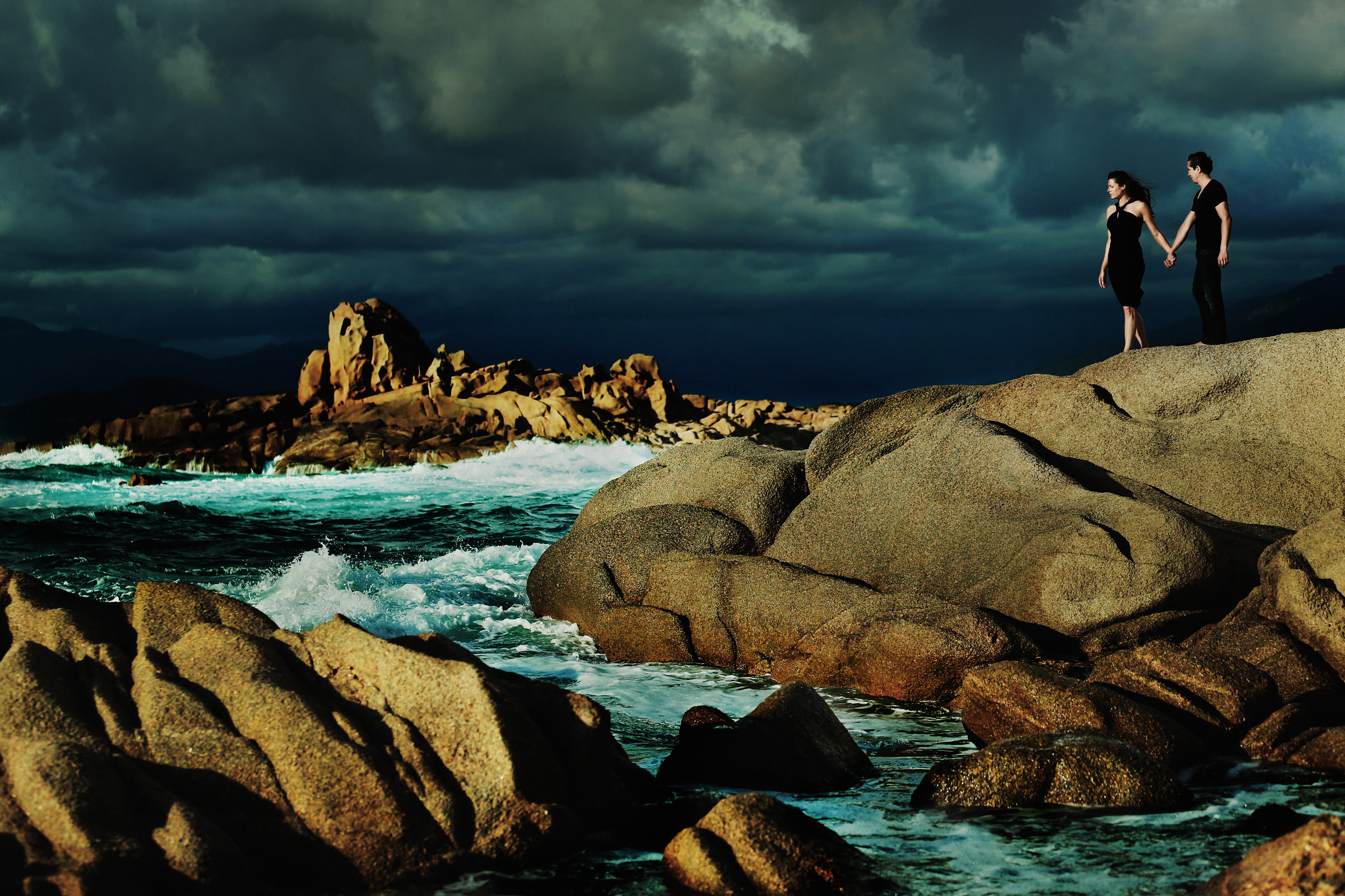 Engagement portrait on rocks by the ocean, by Franck Boutonnet