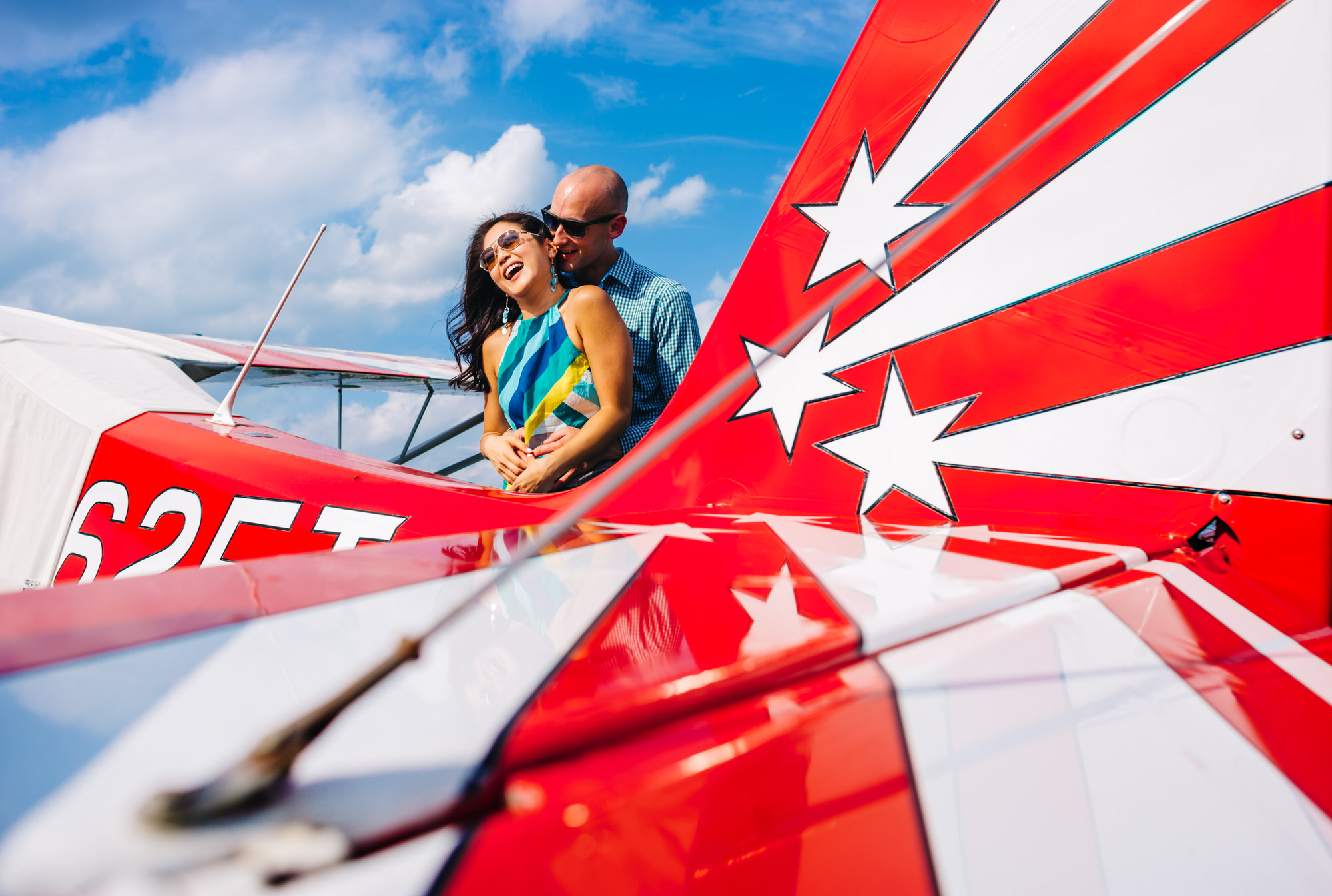 Engagement portrait against red and white airplane wing - photo by Ken Pak