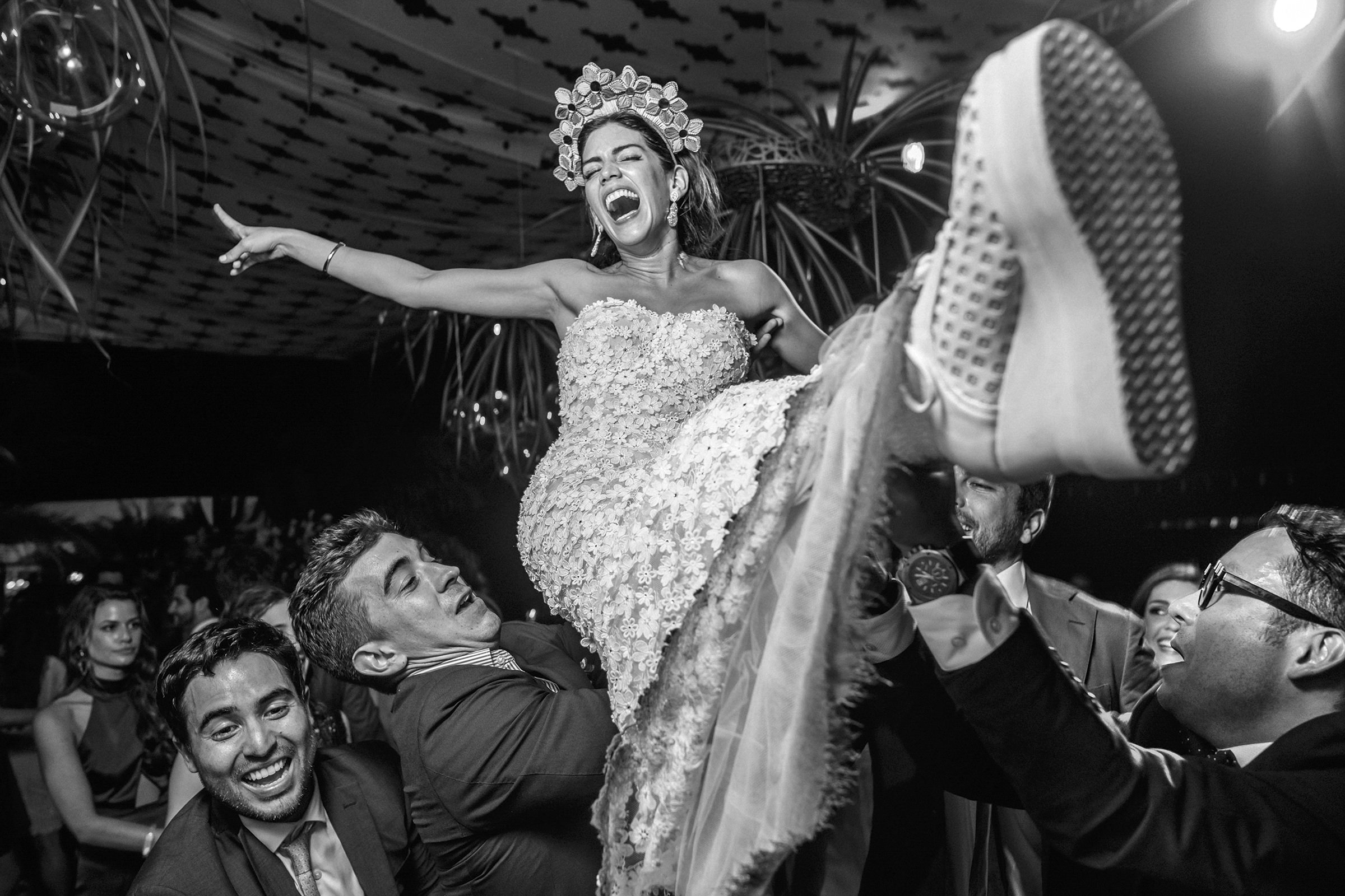 Bride laughing carried on shoulders of guests during reception, by Victor Marti, El Marco Rojo