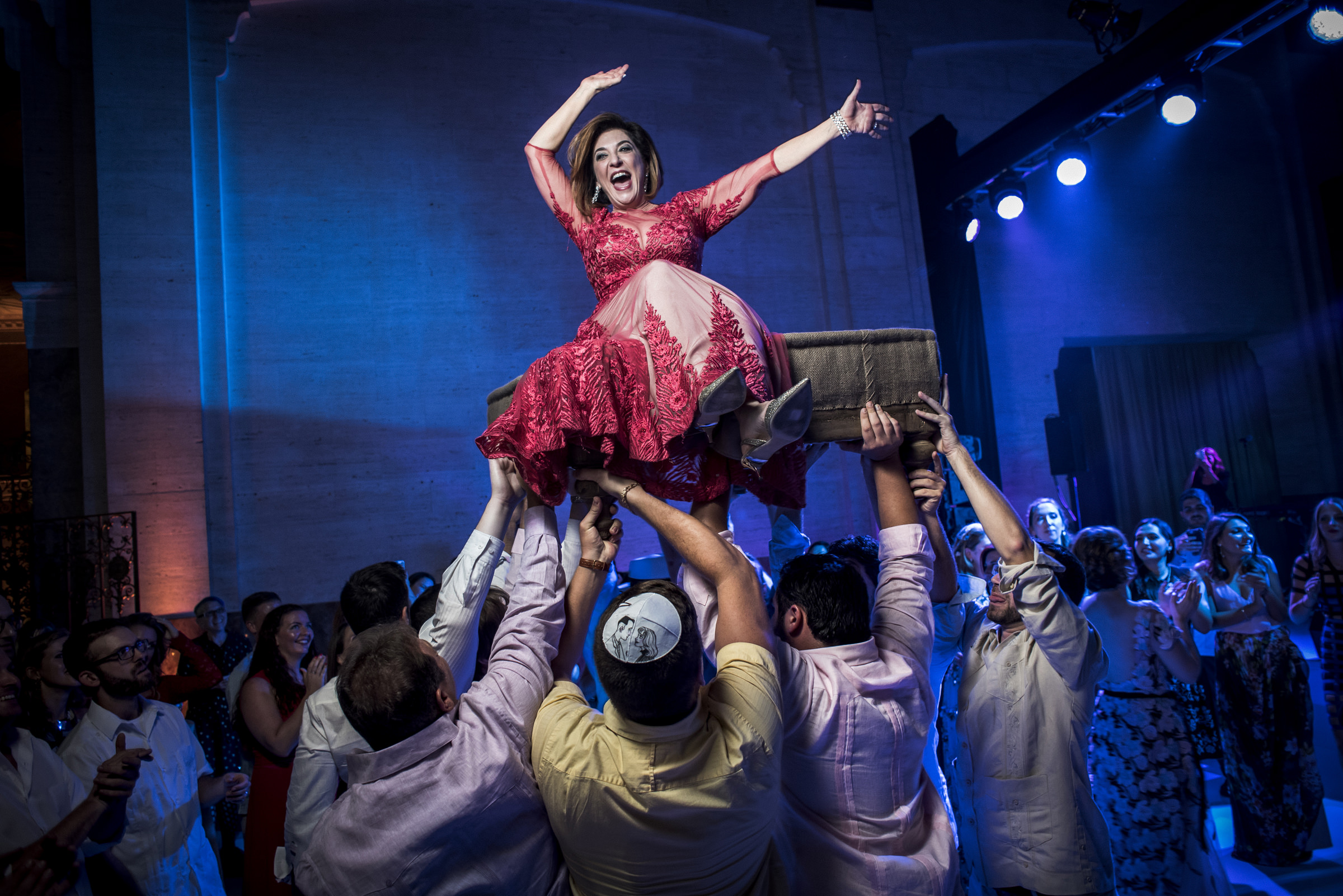 Ecstatic mother in red on divan during hora, by Victor Marti, El Marco Rojo Photography
