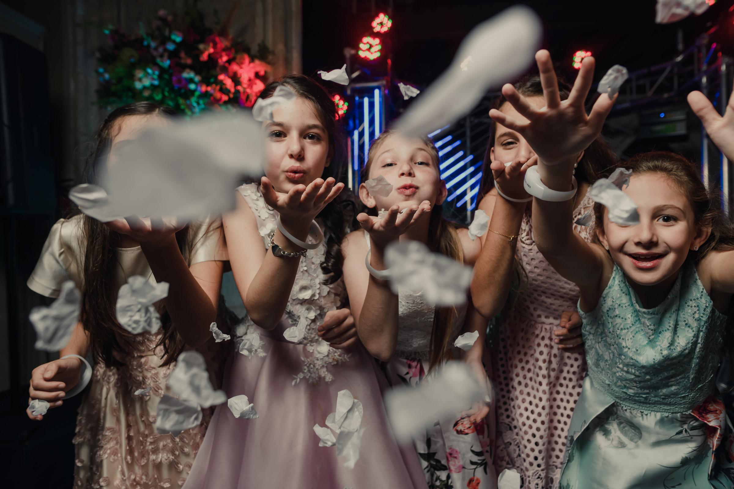 Flower girls blowing petals at camera, by Victor Marti, El Marco Rojo Photography