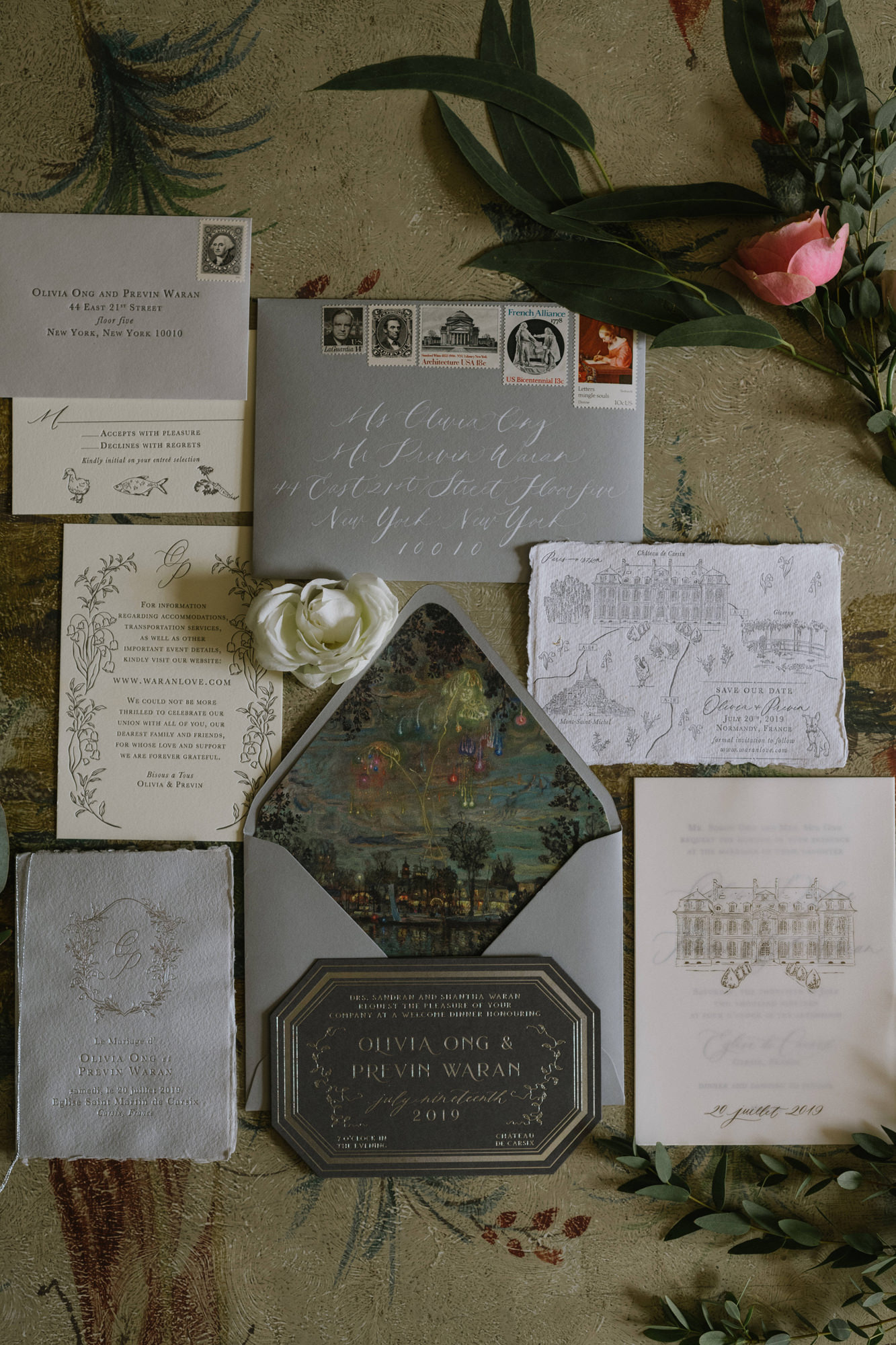 Flatlay of silver, black and ivory wedding invitations by Thierry Joubert