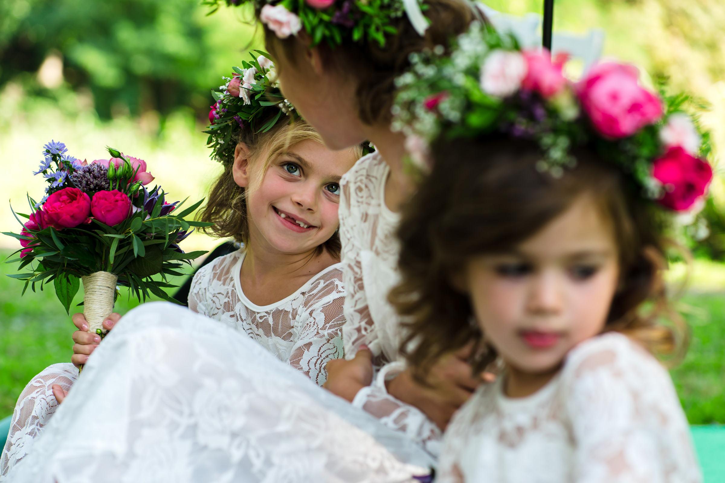 Flower girls in colorful floral crowns smiling at each other, photo by Philippe Swiggers