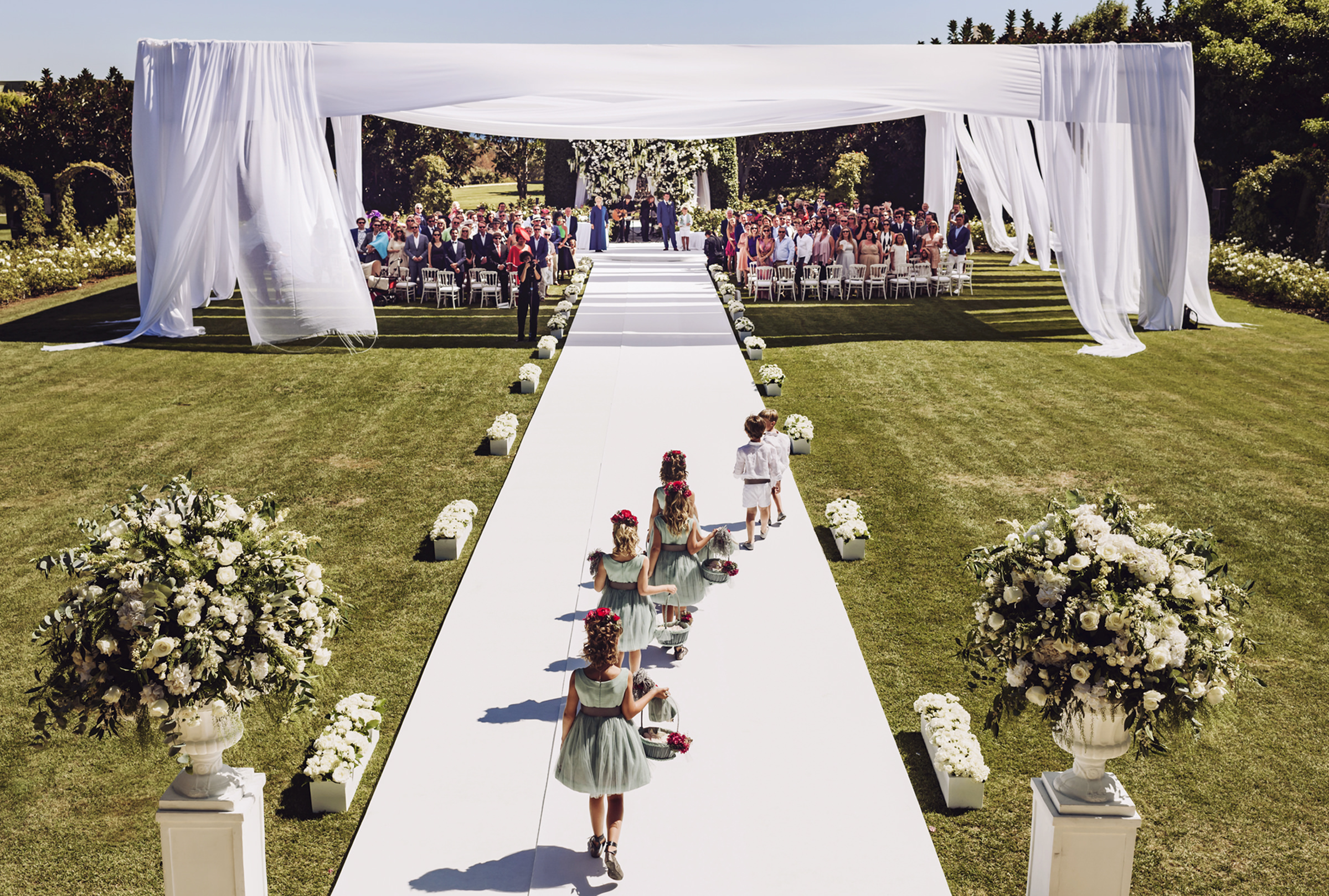 Flower girls and ringbearers walking towards garden ceremony, by Victor Marti, El Marco Rojo Photography