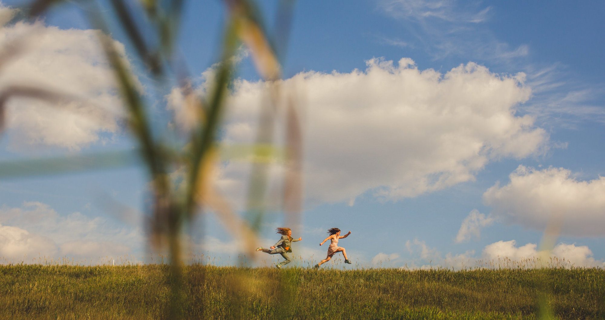 Fun photo of couple running in distance, by Jeff Newsom