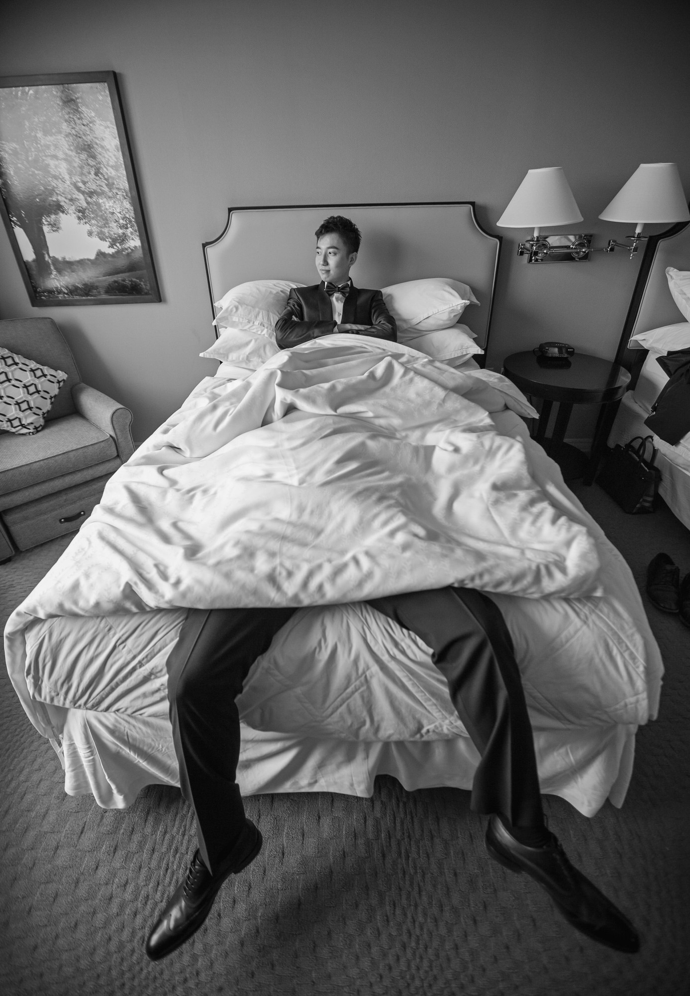 Funny photo of groom and legs in bed - photo by Ken Pak