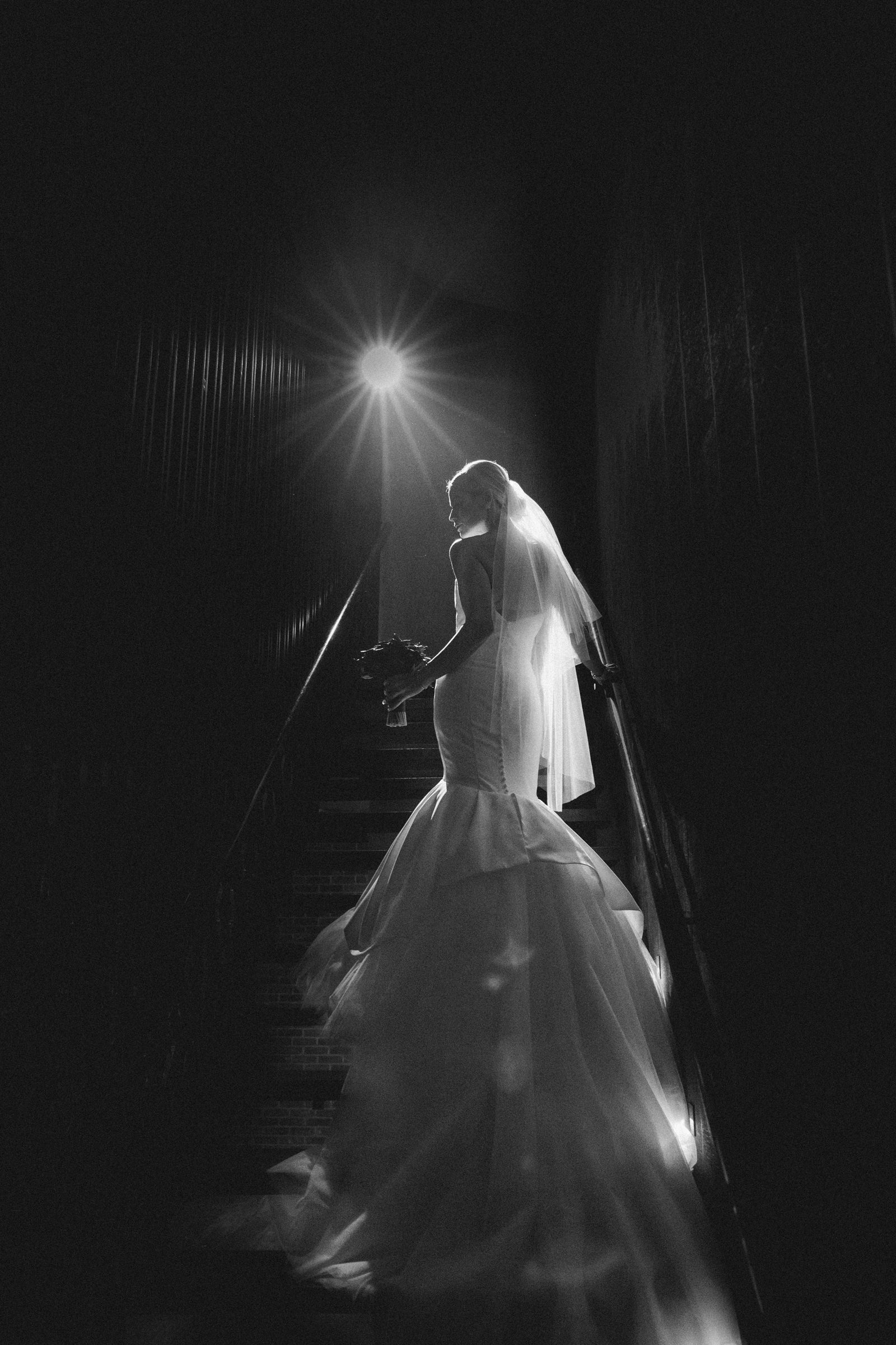 Glamorous bride ascending stairs - Photo by Susan Stripling Photography