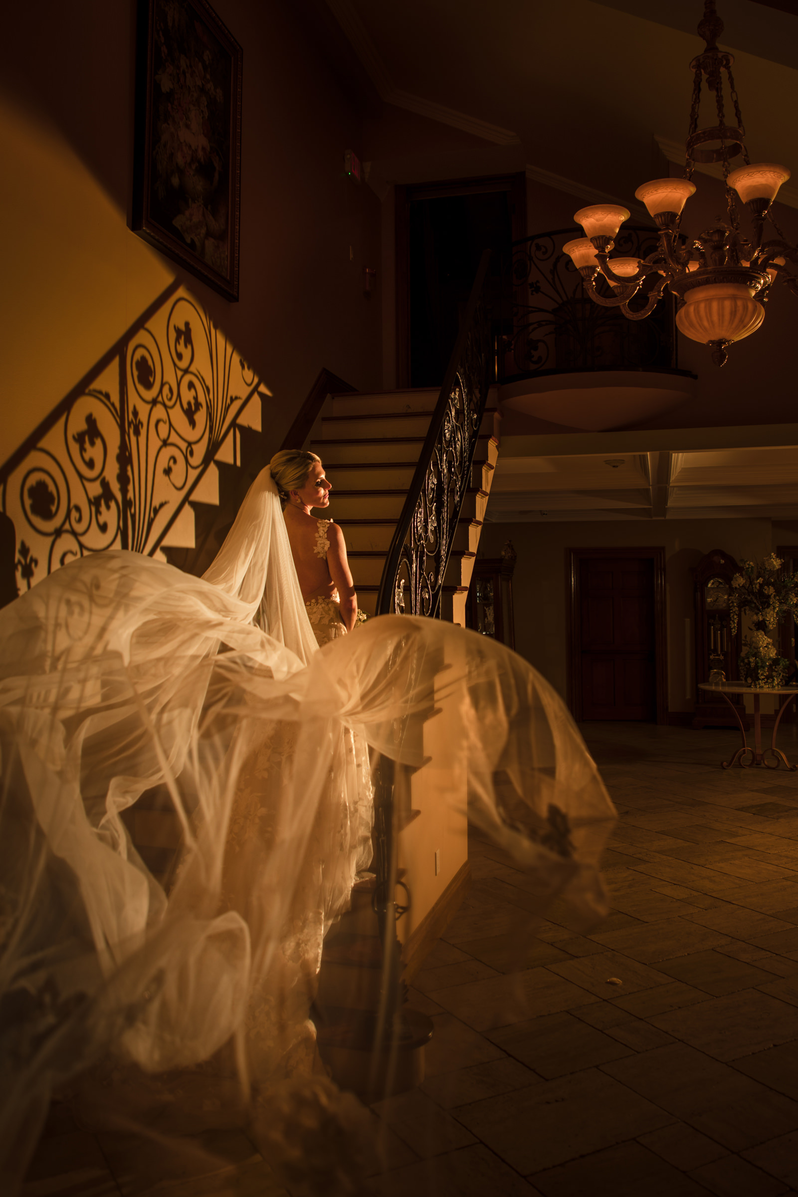 Glamorous bride  with dramatic veil on staircase - Photo by Susan Stripling Photography