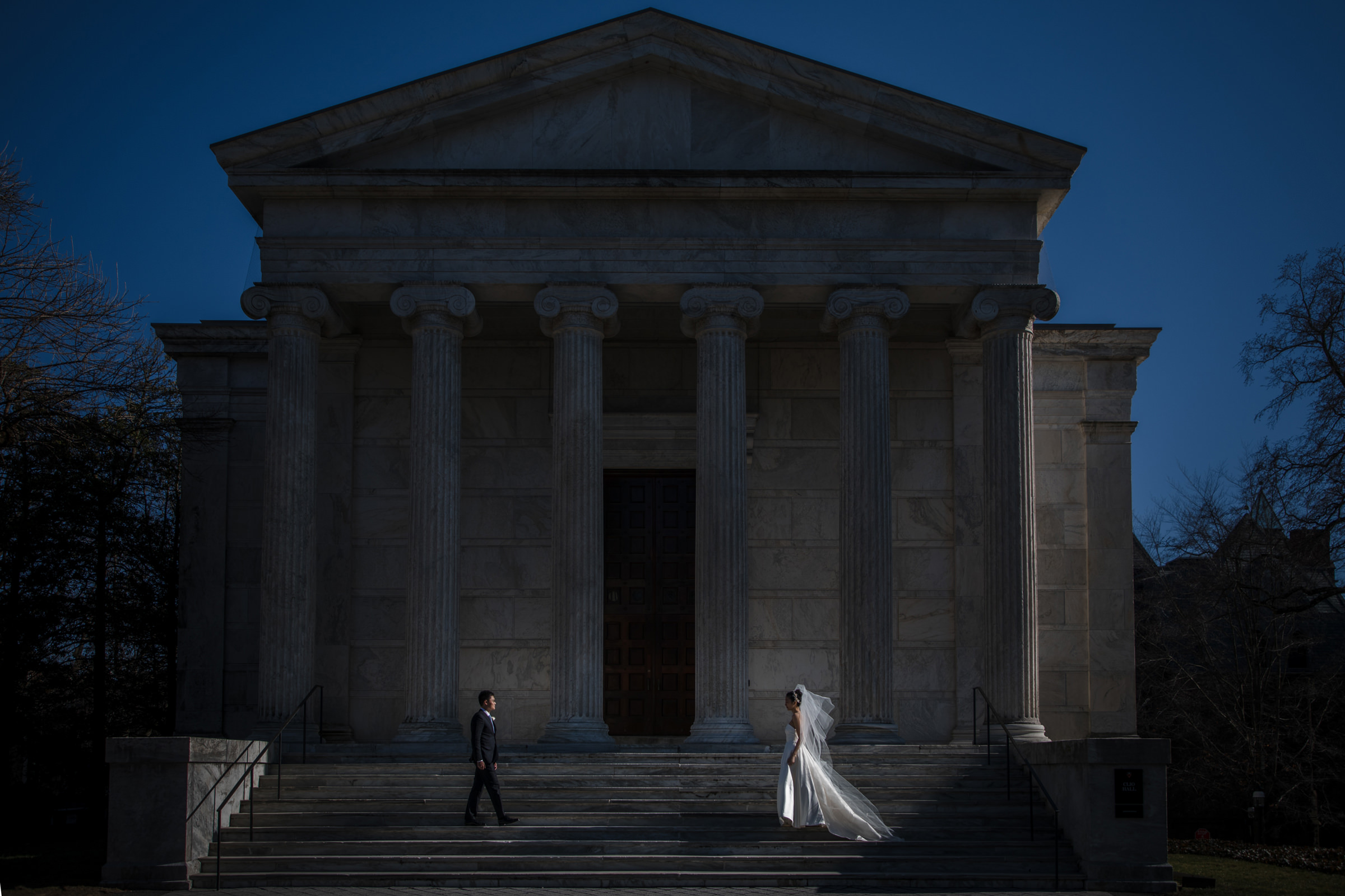 Bride and groom against classic architecture - Photo by Susan Stripling Photography
