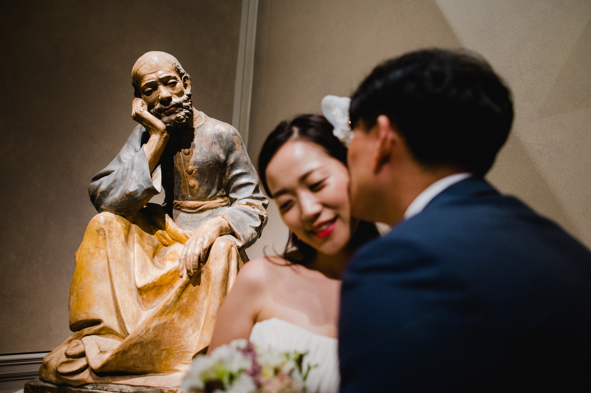 Creative composition of bride and groom with statue - photo by Ken Pak