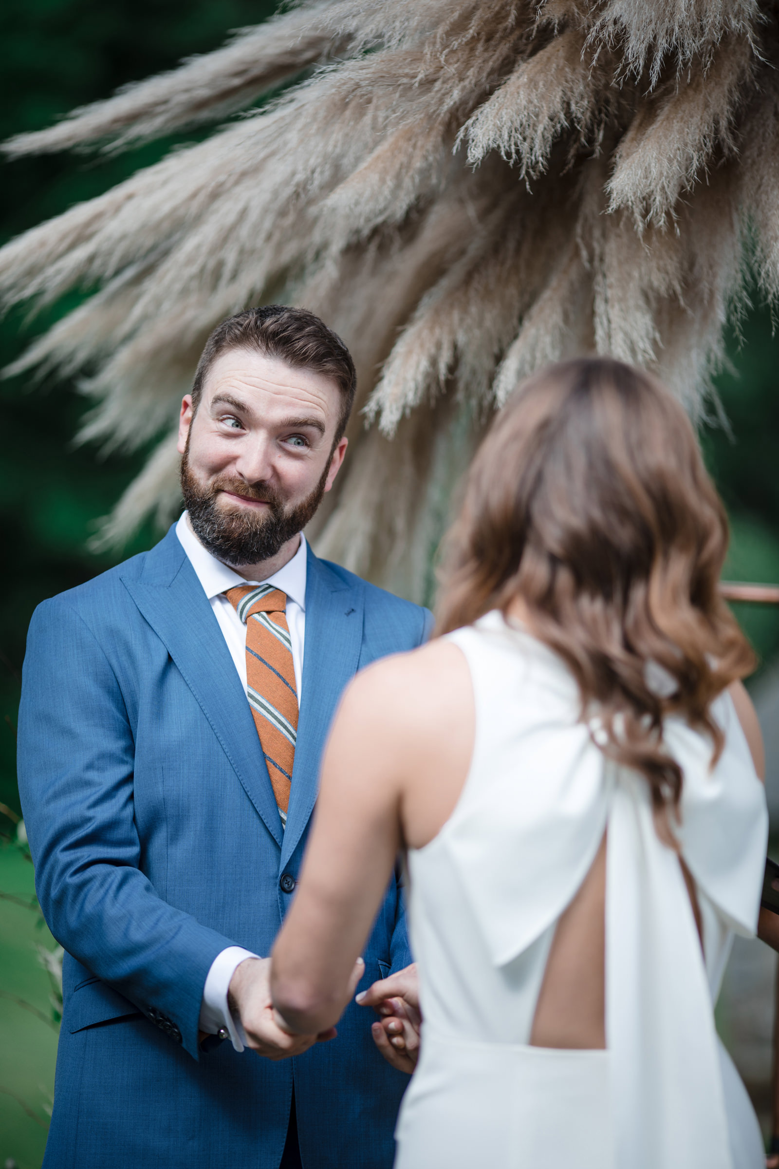 Groom reacts to bride at wedding ceremony, by Susan Stripling