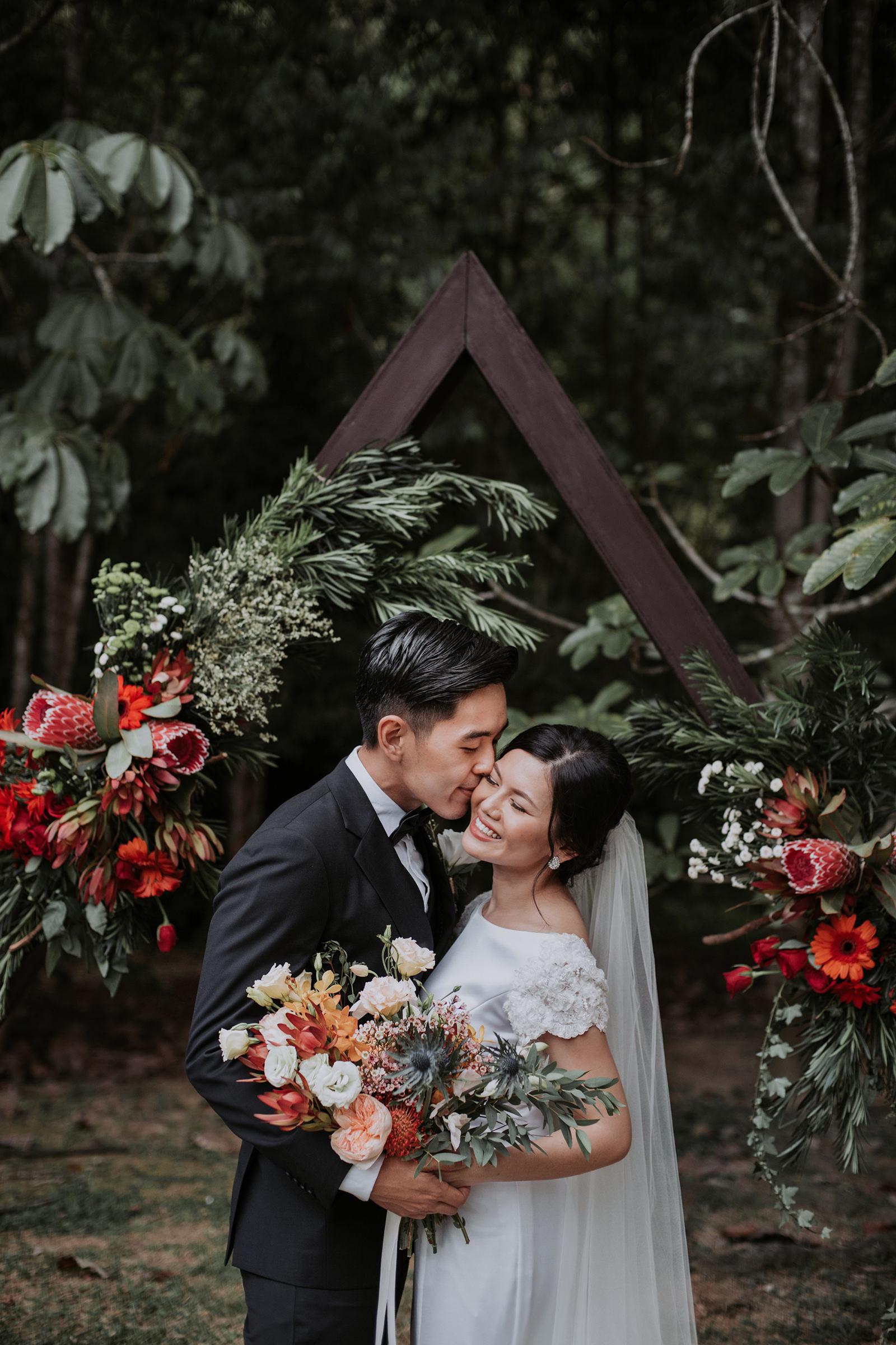 Groom kisses bride on the cheek. Photo by MunKeat Photography Studio