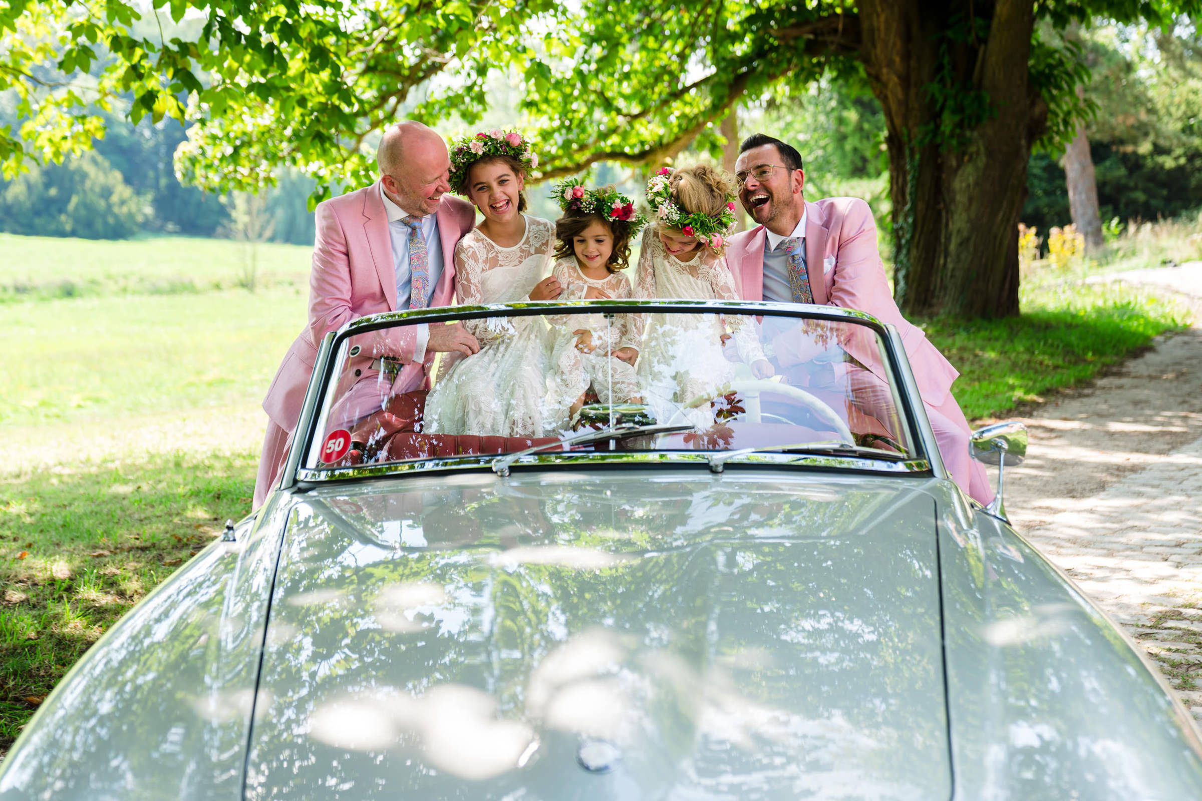 Portrait of grooms and flower girls on convertible, photo by Philippe Swiggers