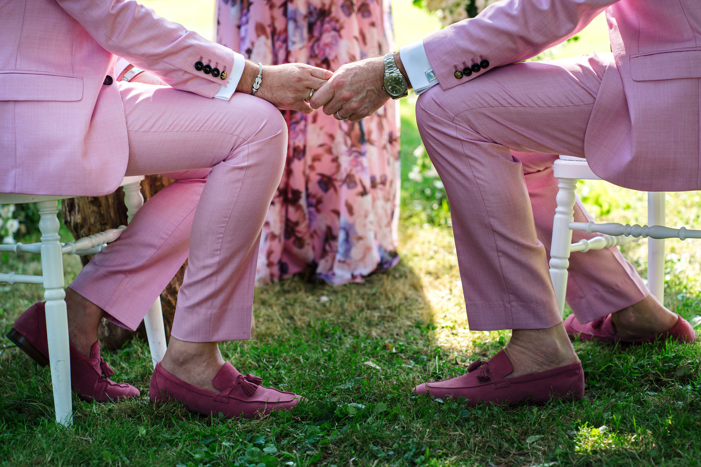Grooms in pink suits hold hands at wedding ceremony, photo by Philippe Swiggers