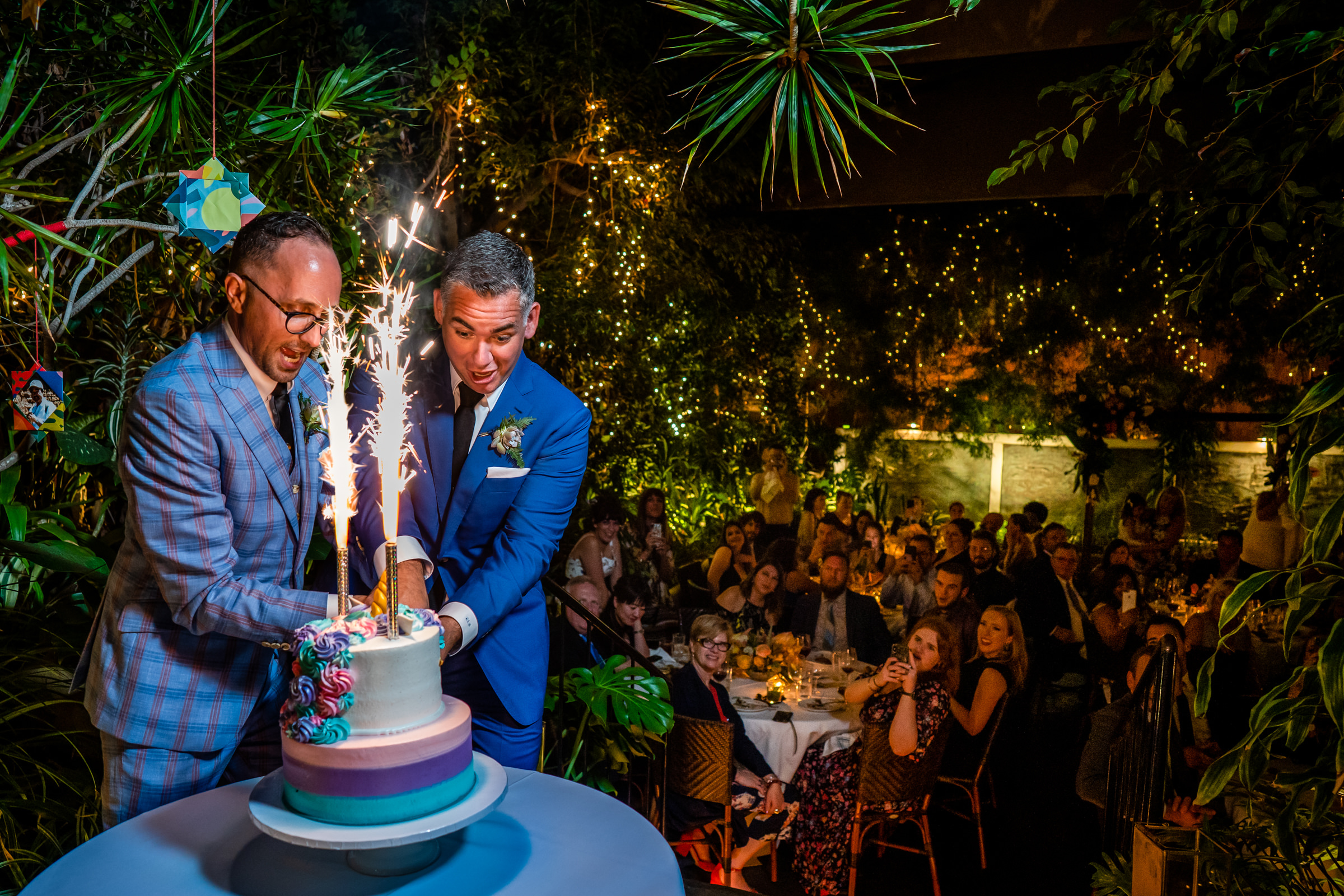 Grooms try to cut cake with sparklers - photo by Bee Two Sweet