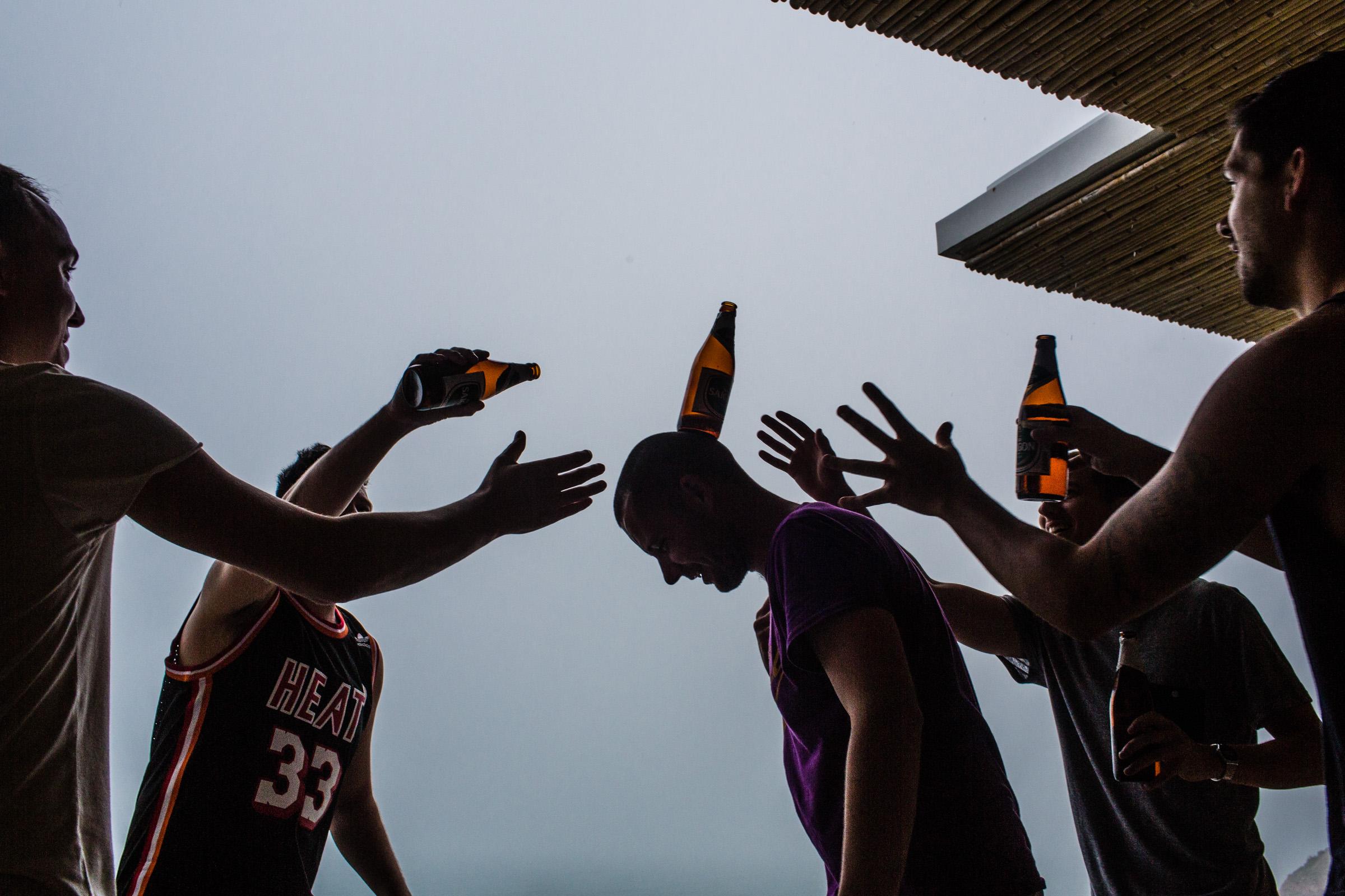 Groomsmen horsing around with beer - Photo by Wainwright Weddings
