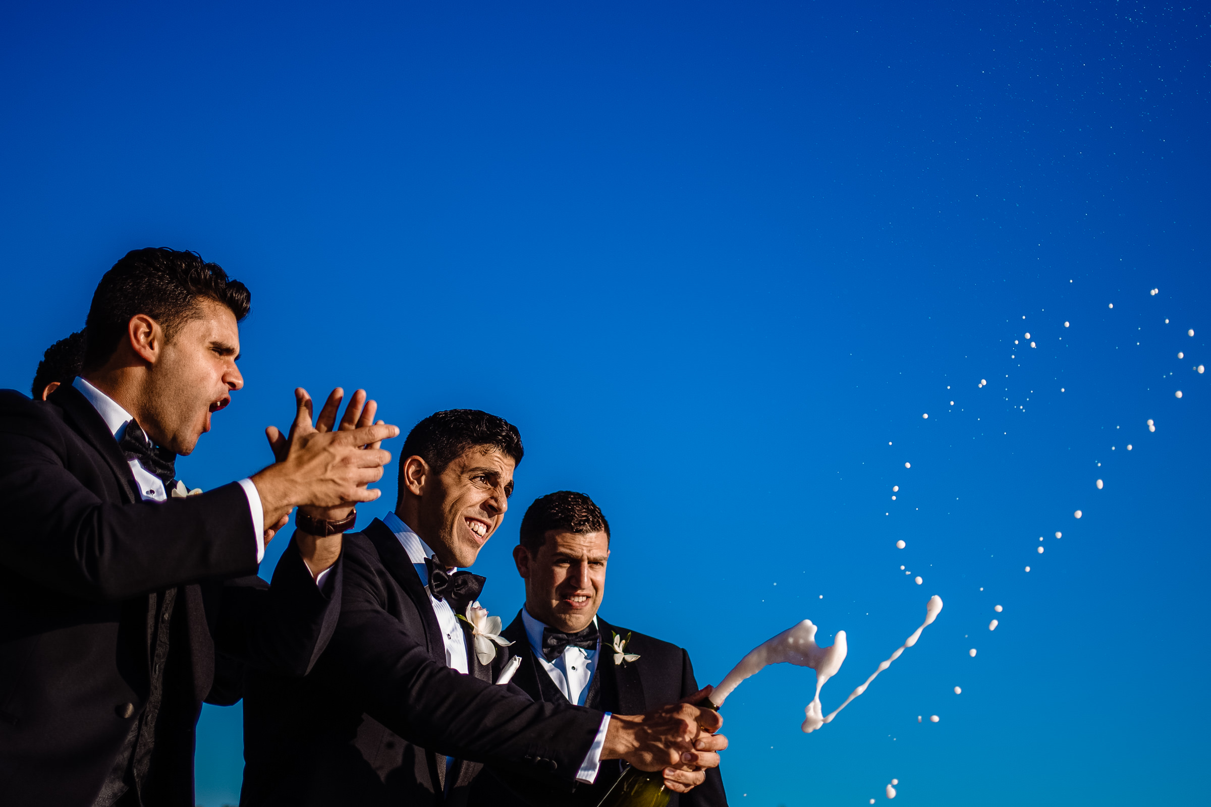 Groomsmen popping champagne - Photo by Wainwright Weddings