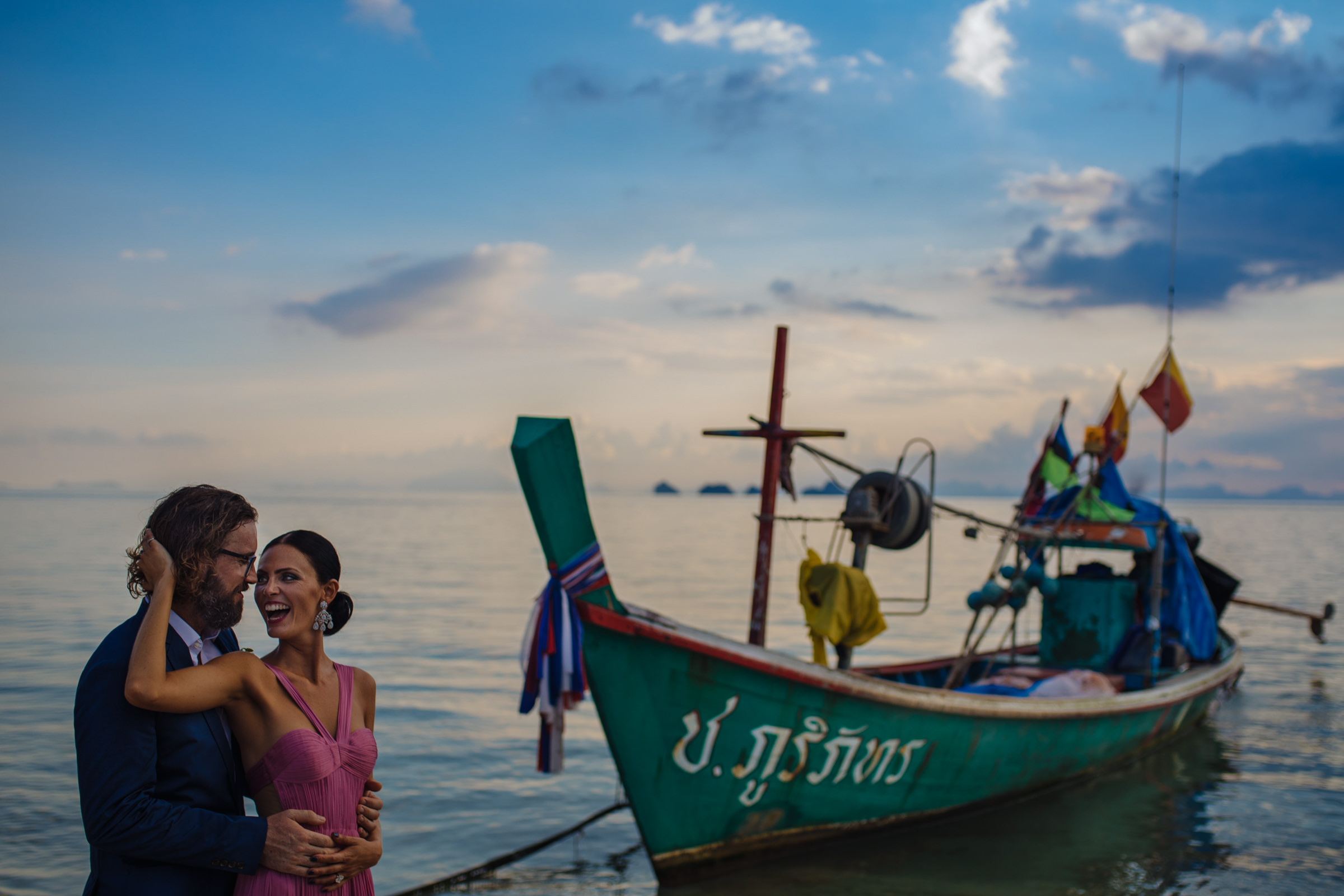 Happy couple waterside with Thai boat - Photo by Wainwright Weddings