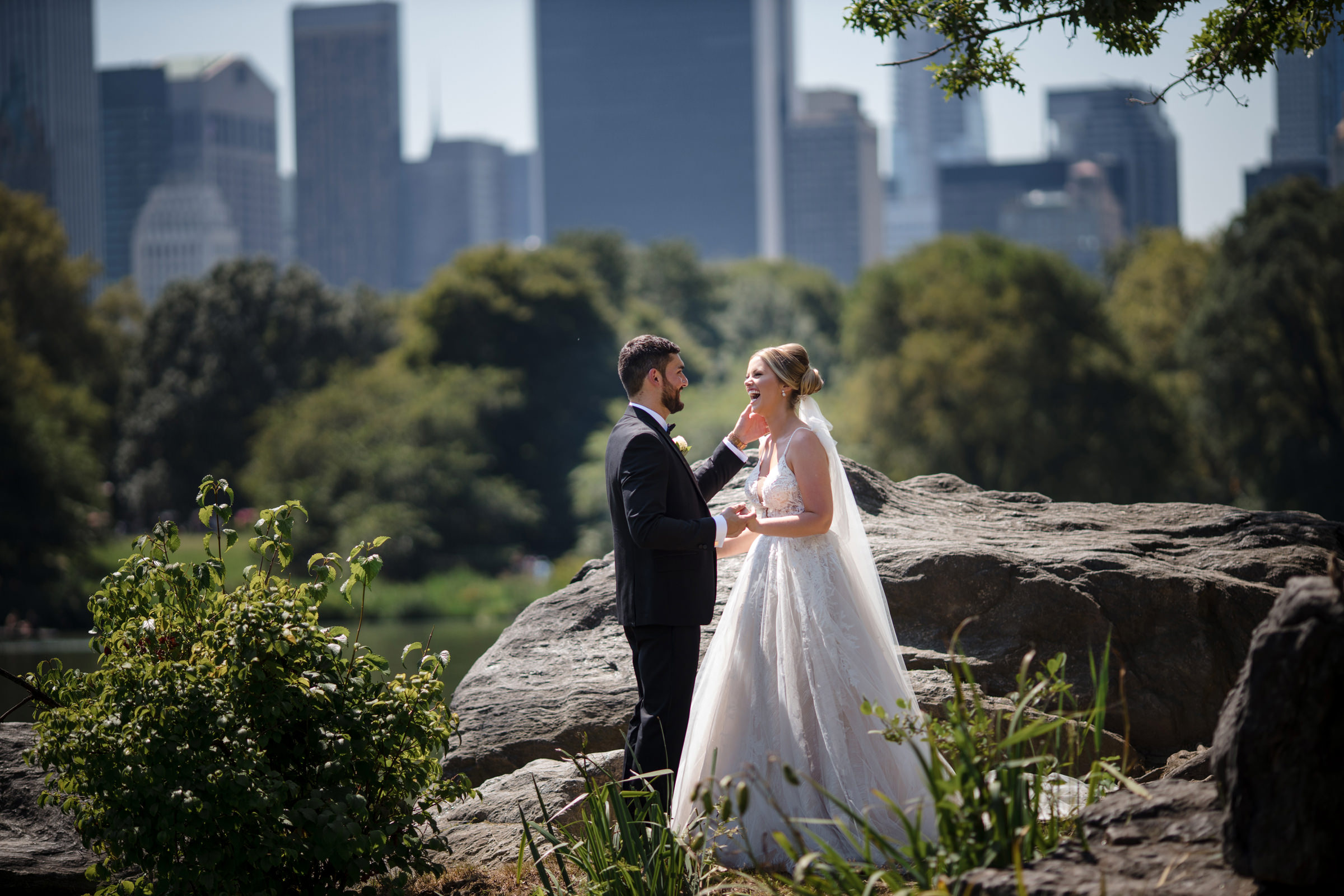 Joyful bride and groom in Central Park against NYC cityscape, photo by Susan Stripling