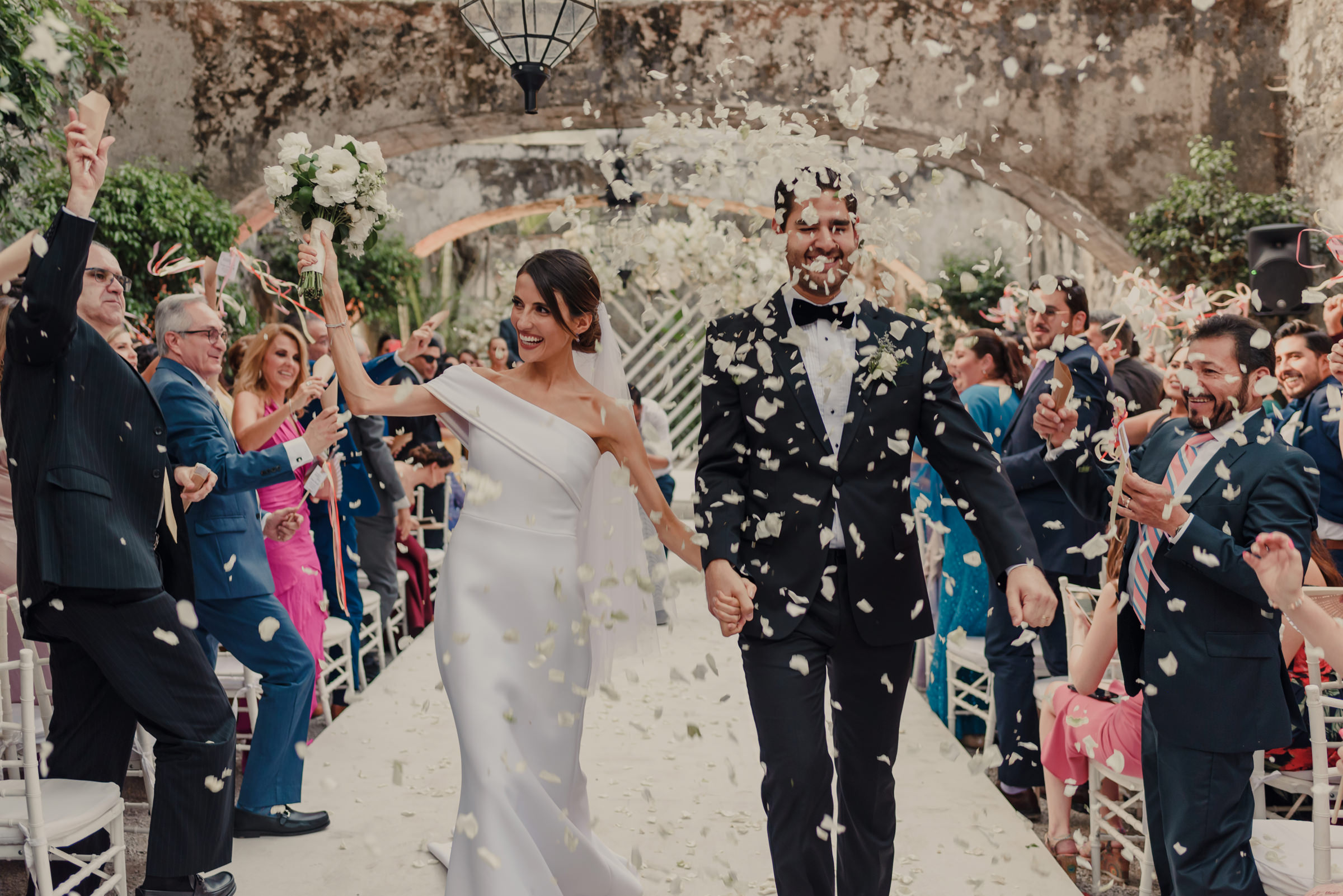 Just married couple leaving ceremony in shower of flowers - photo by El Marco Rojo