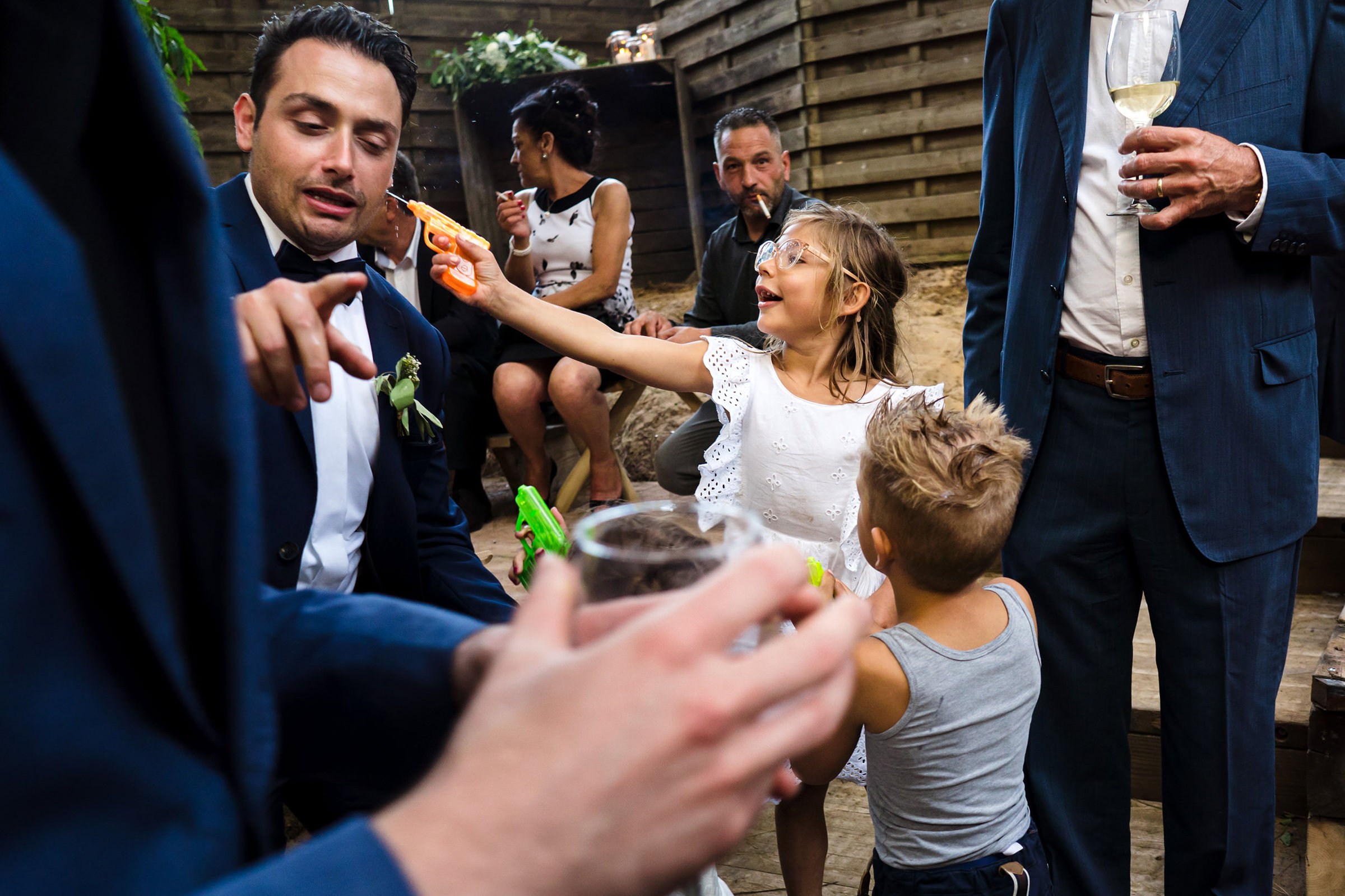 Funny photo of little girl shooting spraygun at groom, photo by Philippe Swiggers