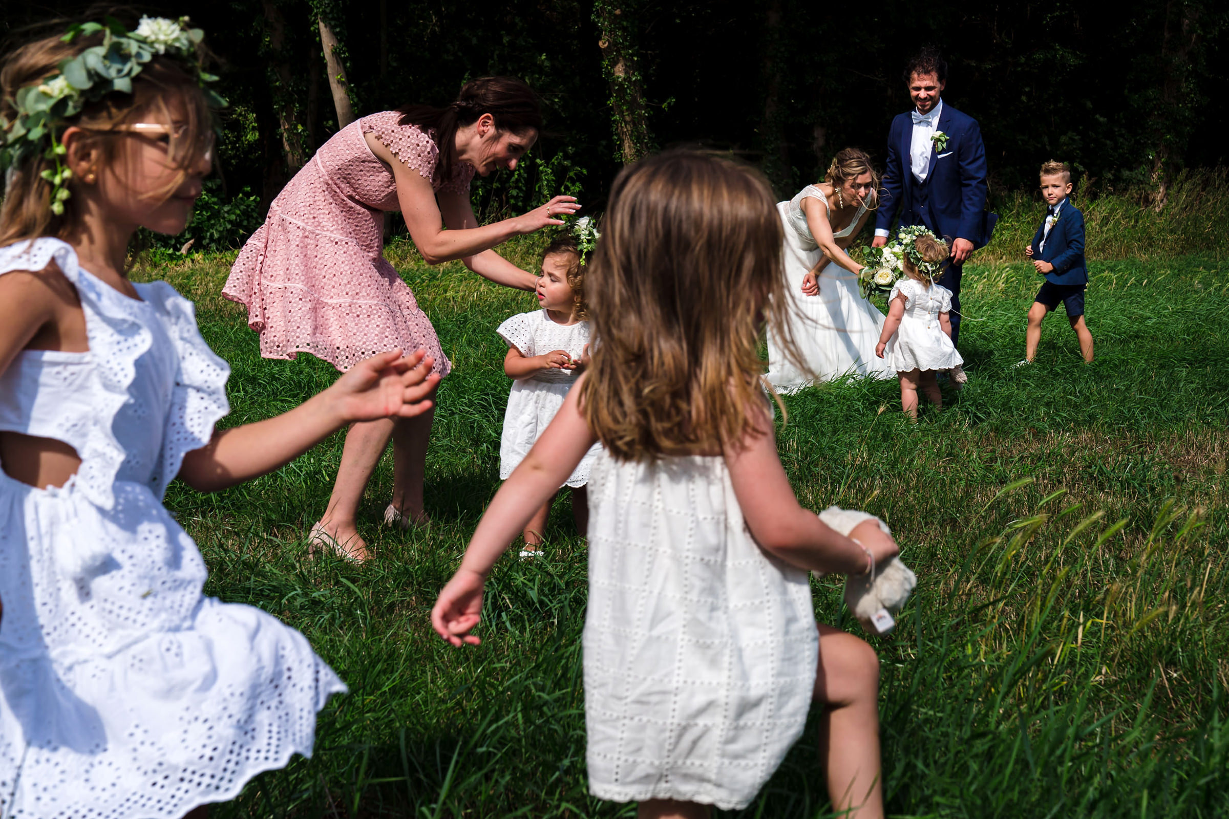 Flower girls and couple play in field, photo by Philippe Swiggers