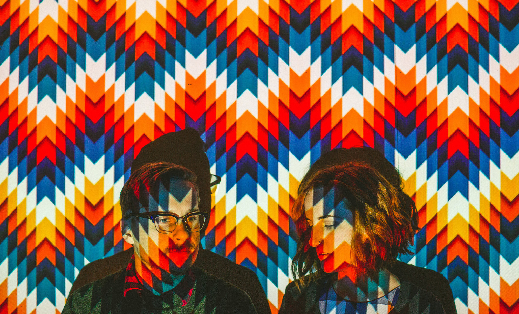 Engagement portrait of couple on colorful chevron light projected wall, by Jeff Newsom