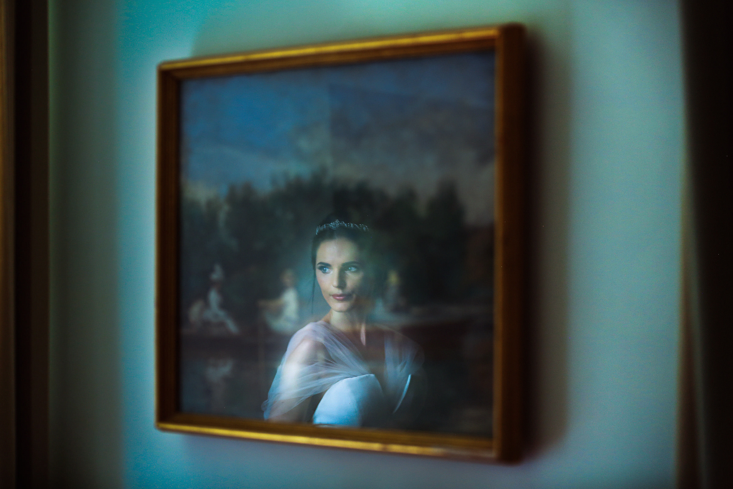 Reflection of bride in framed photo on wall, by Franck Boutonnet