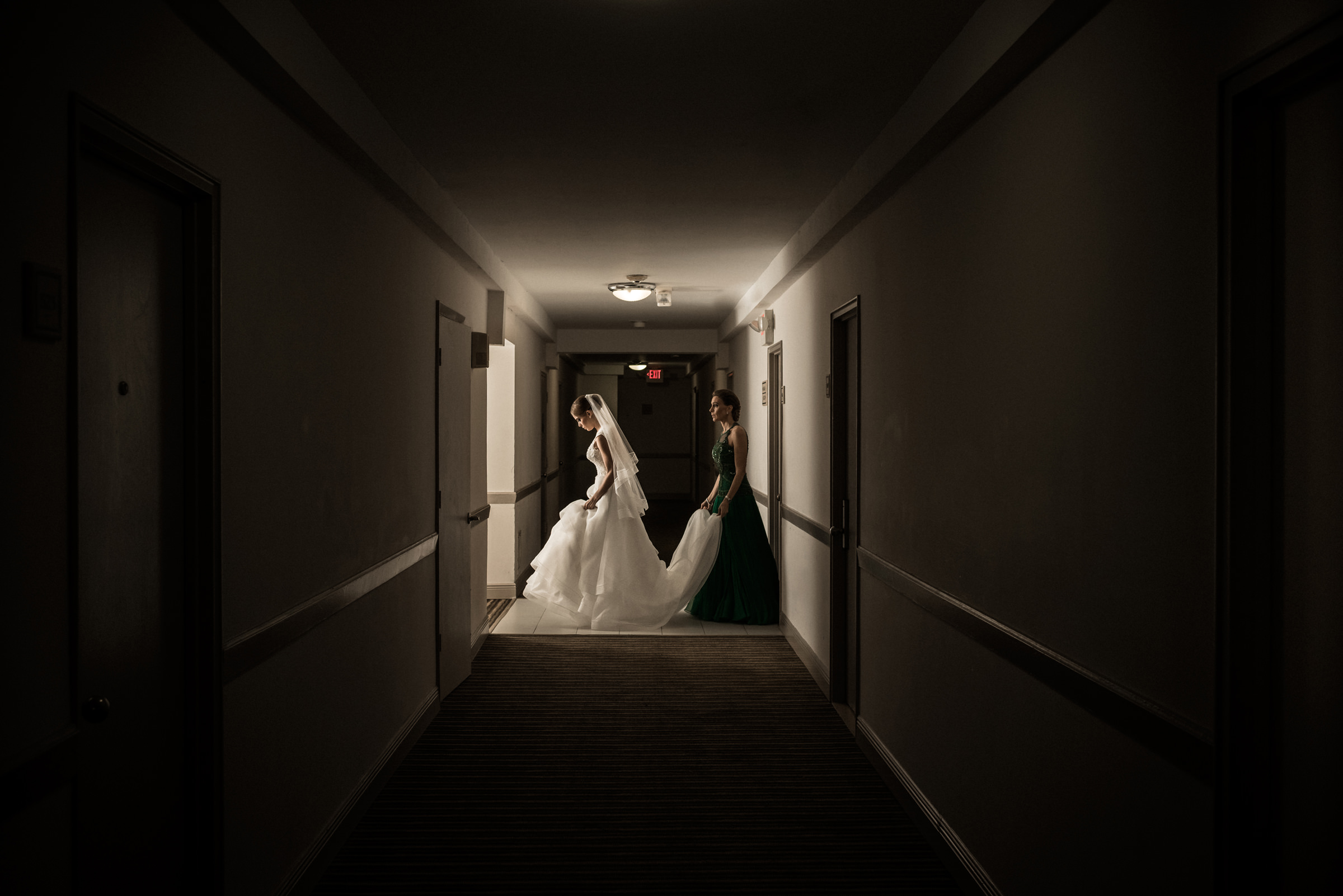 Mother holds brides train in hotel hallway - photo by El Marco Rojo