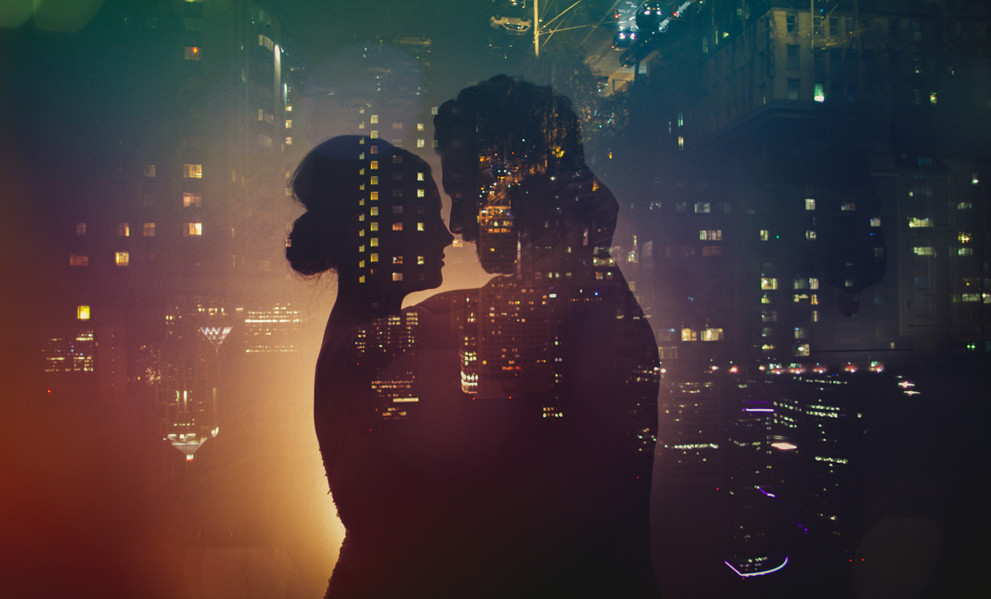 Multiple exposure silhouette of couple against city lights, by Jeff Newsom