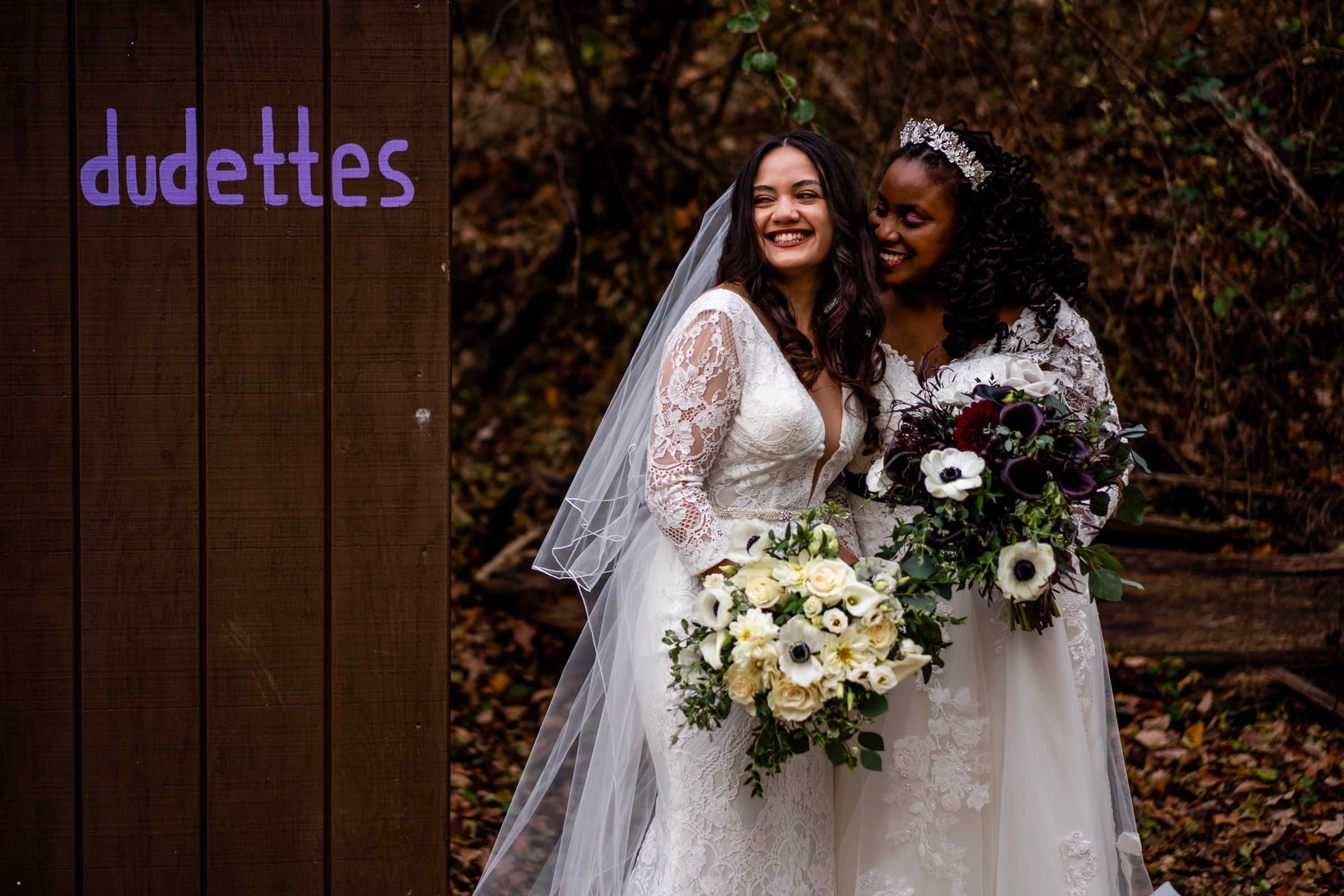 Portrait of two brides in lace gowns with large bouquets by Bee Two Sweet