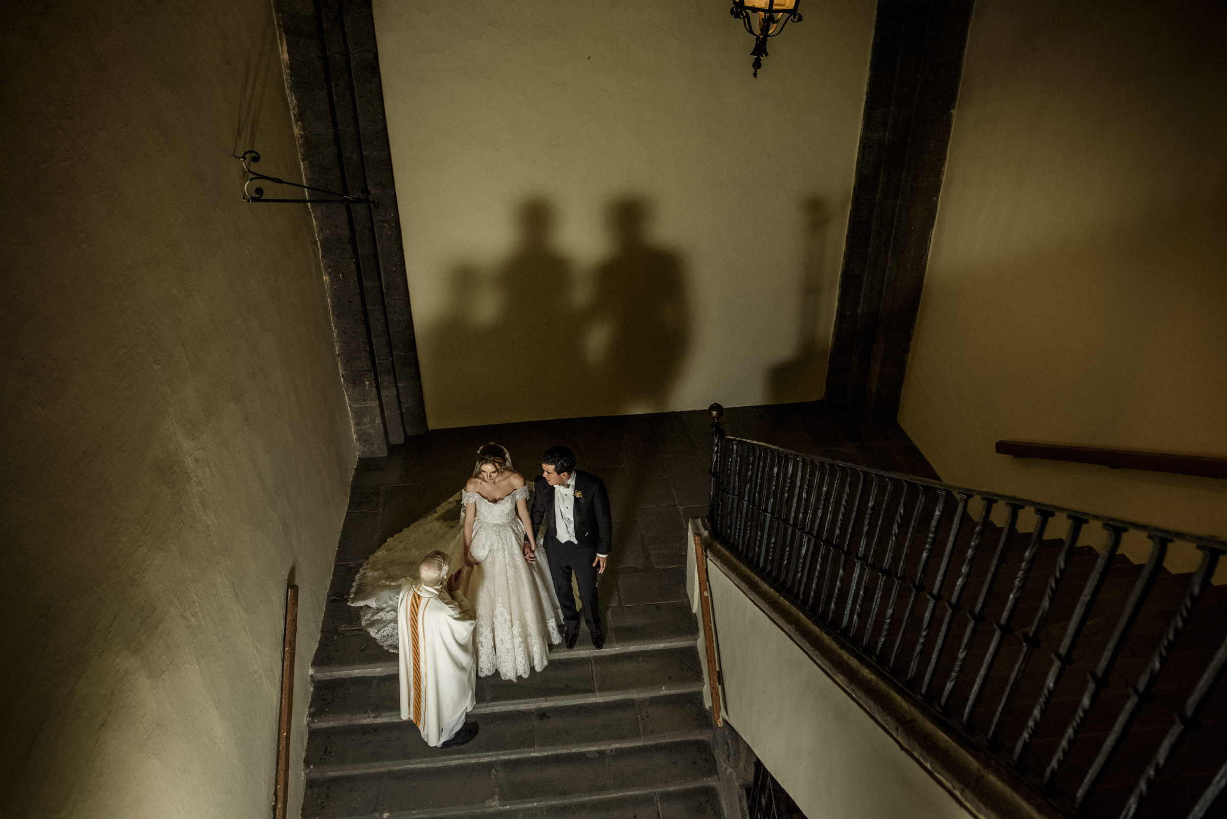 Bride and groom with priest on stairway - photo by El Marco Rojo