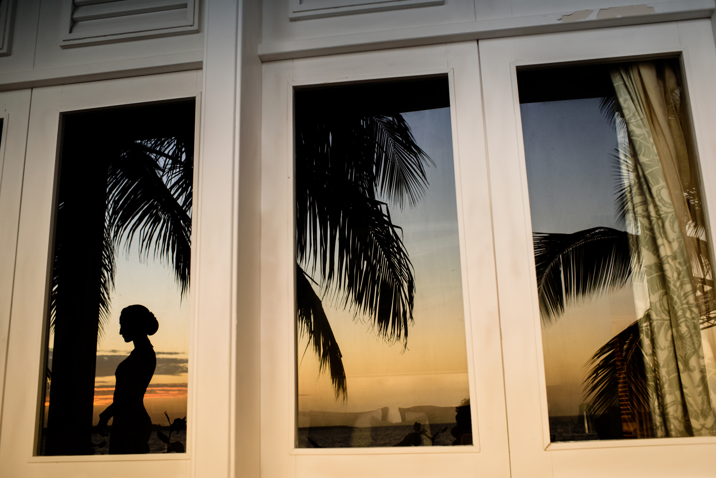 Silhouette of bride in window with palm trees - photo by El Marco Rojo